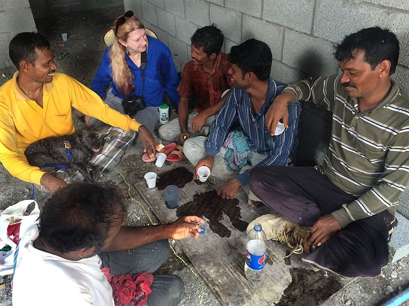 Photojournalist Sherrlyn enjoys hearing a story from Bangladesh workers. See her dog in the man's lap?