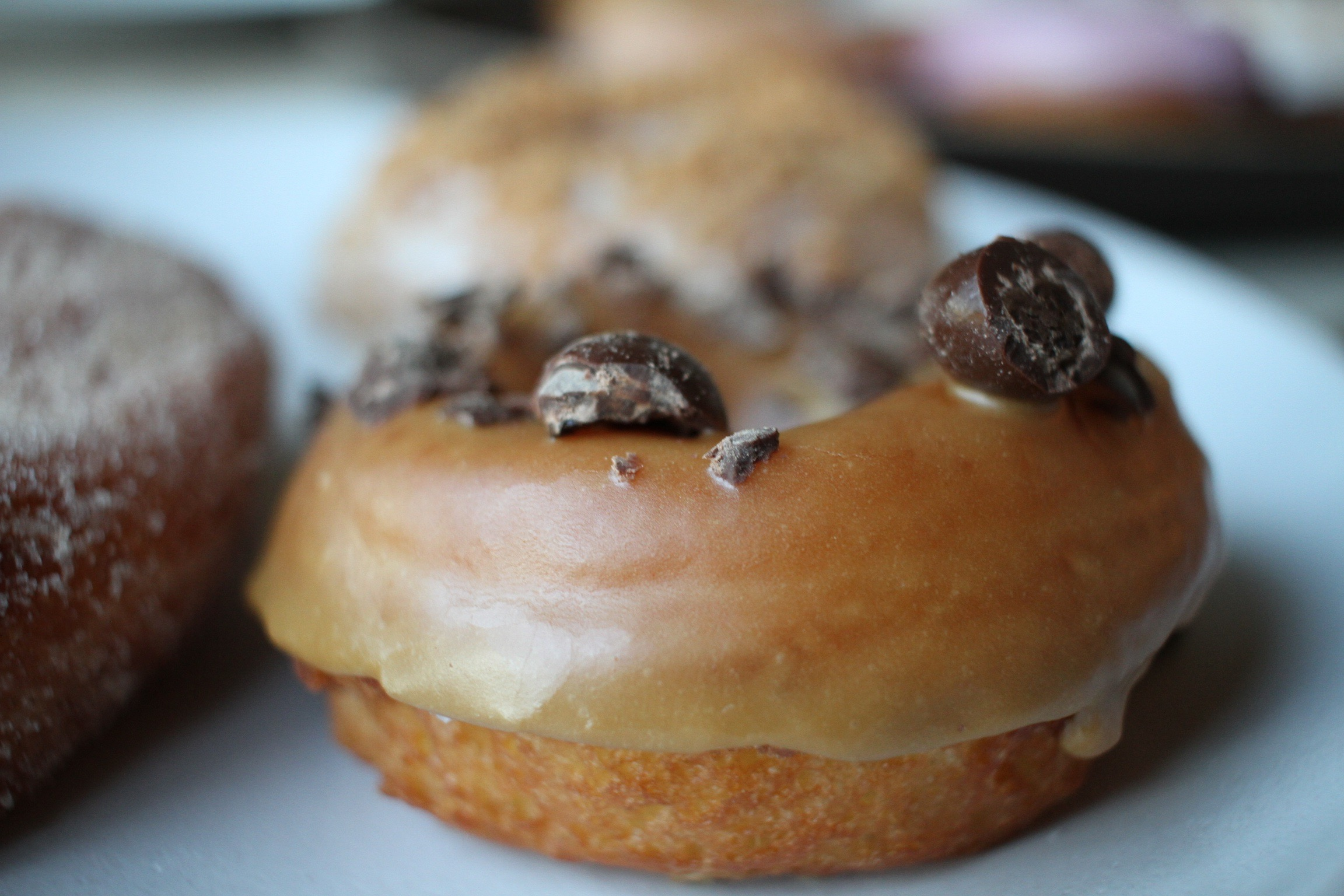 raised donut with glaze and chocolate pieces
