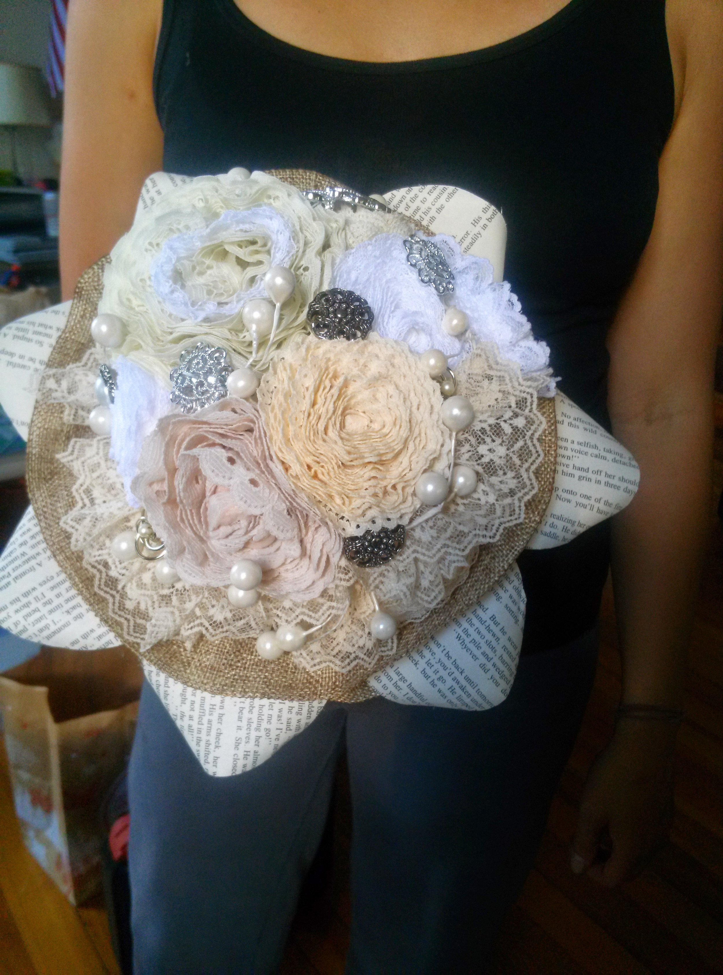 A bride-to-be came to us with an idea and some supplies. She buttons and brooches from her grandmother and lace from an old friend, which she dreamed could be her wedding bouquet. By adding a few additional materials and getting a group of girls together, this bouquet came together quite easily! We also made boutineers and corsages to match!