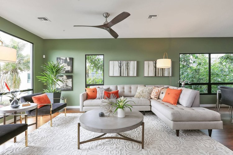 Soft sage makes for a relaxing living space. Orange adds pops of positivity. Via Home Designing .