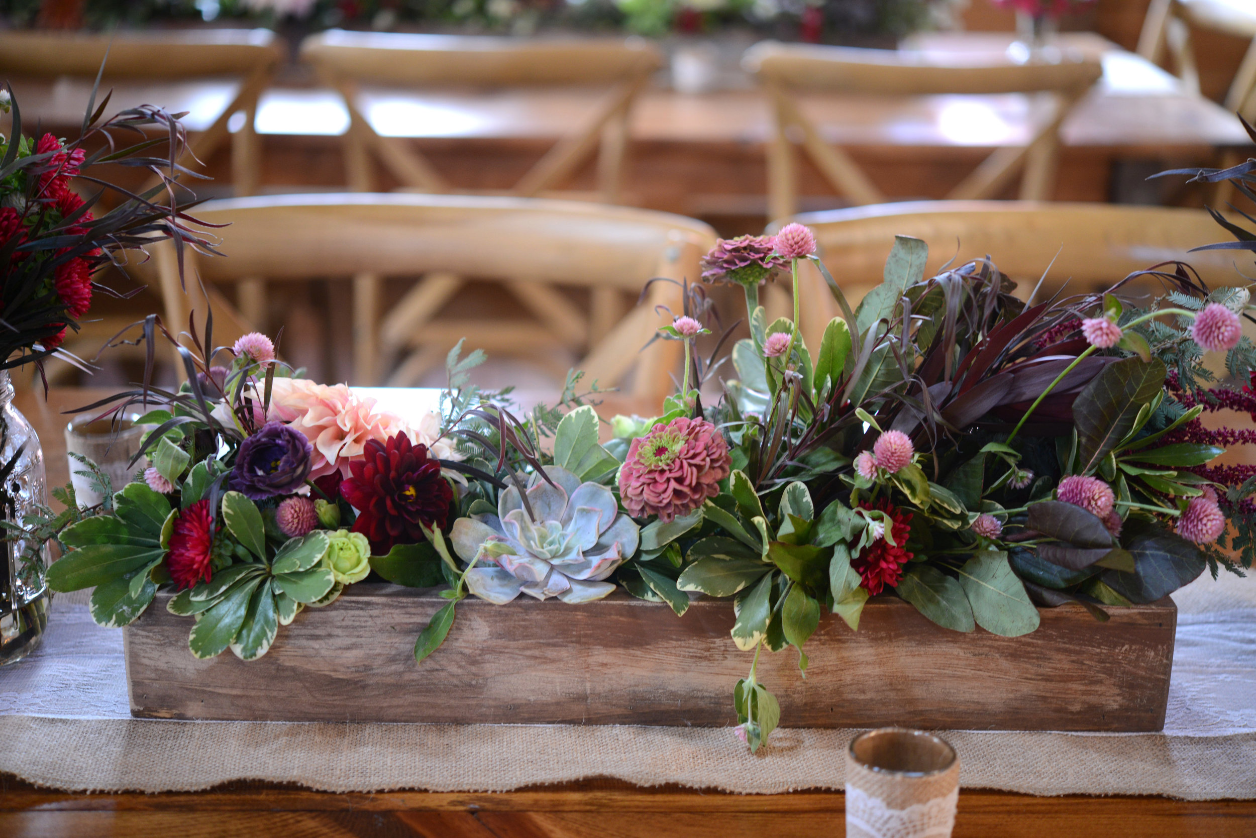 The succulents then worked perfectly in the low and lush, custom-built rustic wood boxes that decorated the long reception tables.