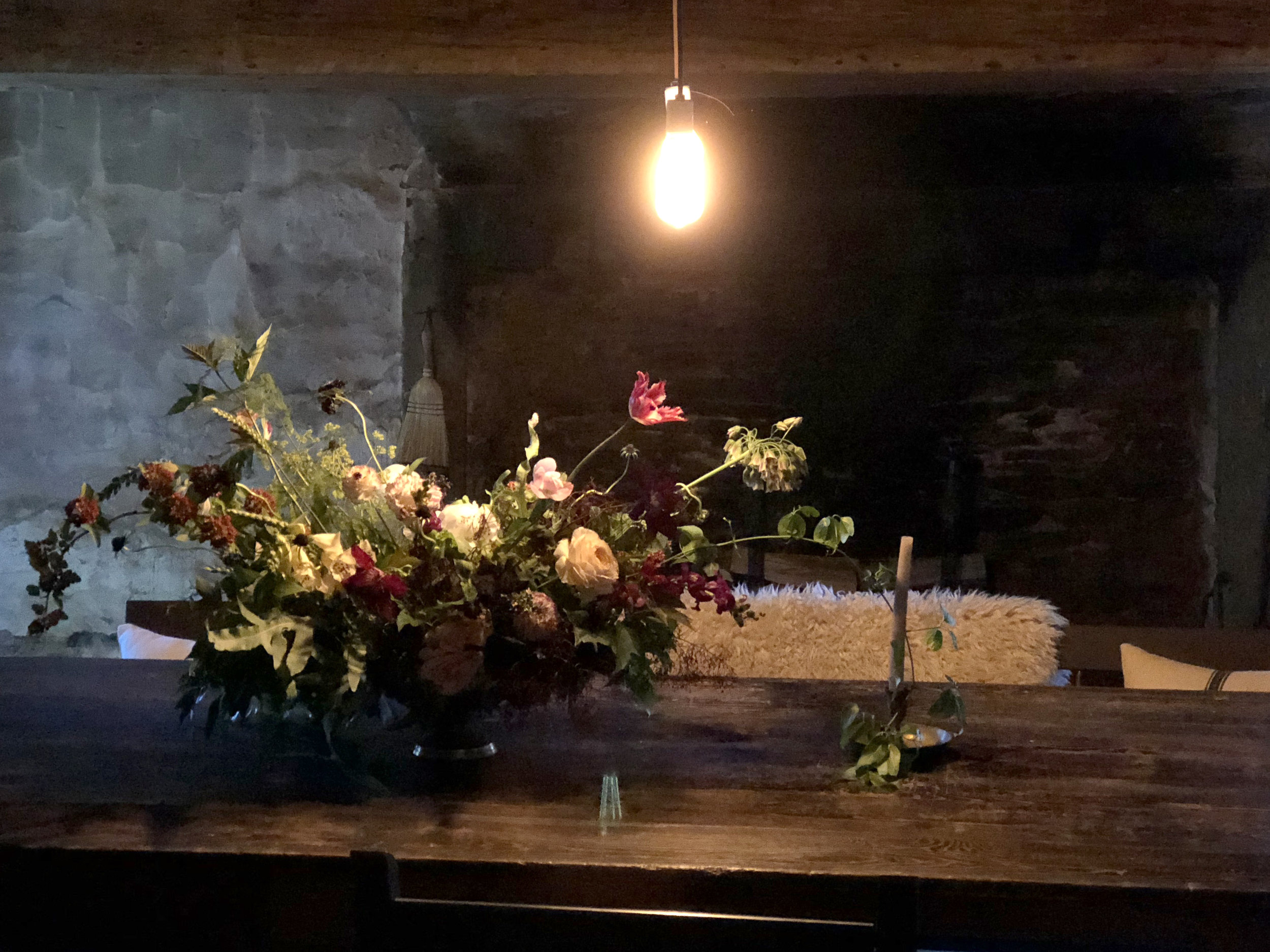 The dining room is in the lower section, which is built into a hill and has limited natural light. Caroline and I quickly agreed to create a 'moody' floral arrangement to play off the vibe of the room. I added clematis vine that was growing around a stone smokehouse on the property to the candle stick and some ninebark branches from the garden to help bring the outdoors inside.