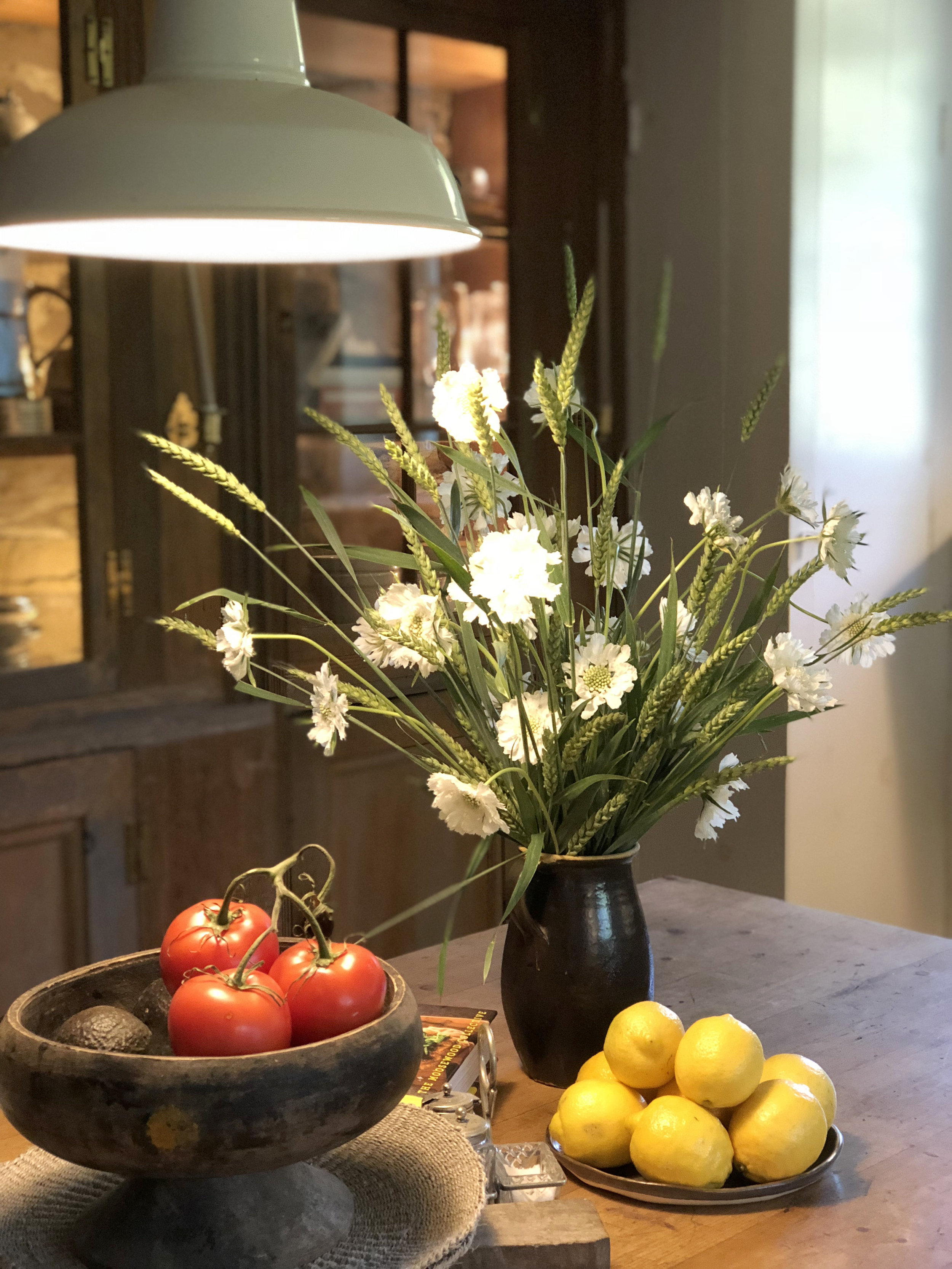 I love the simplicity of white scabiosa and fresh wheat in this sunlit kitchen.