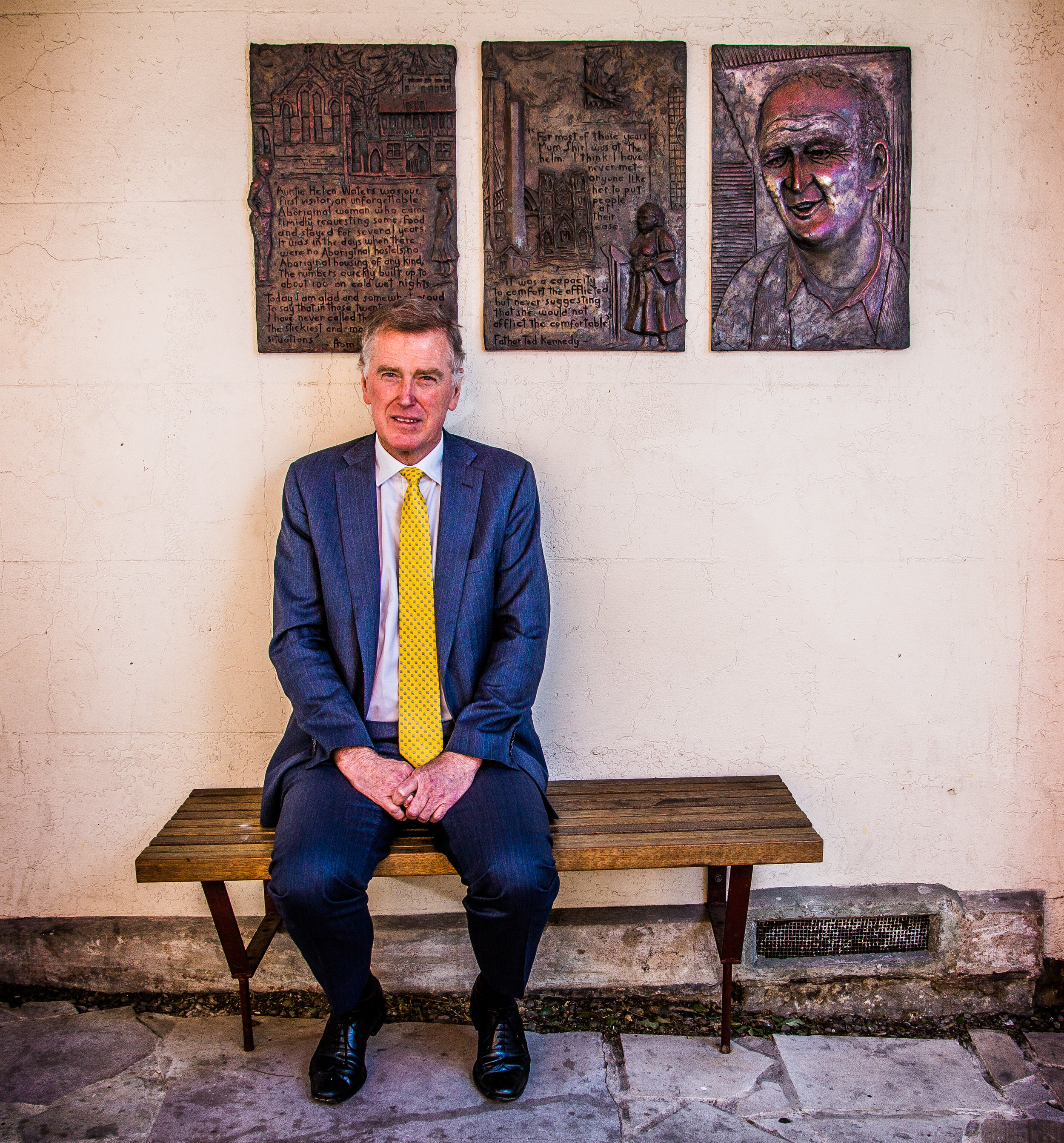 Danny Gilbert in front of a triptych commemorating Danny's friend, long-time Catholic parish priest, Father Ted Kennedy, next to St Vincent's Church in Redfern.