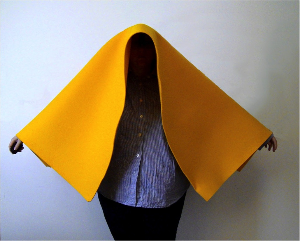 Image of Elizabeth with a large piece of yellow felt draped over her head and shoulders. Her face is not visable and her hands are raised at her sides