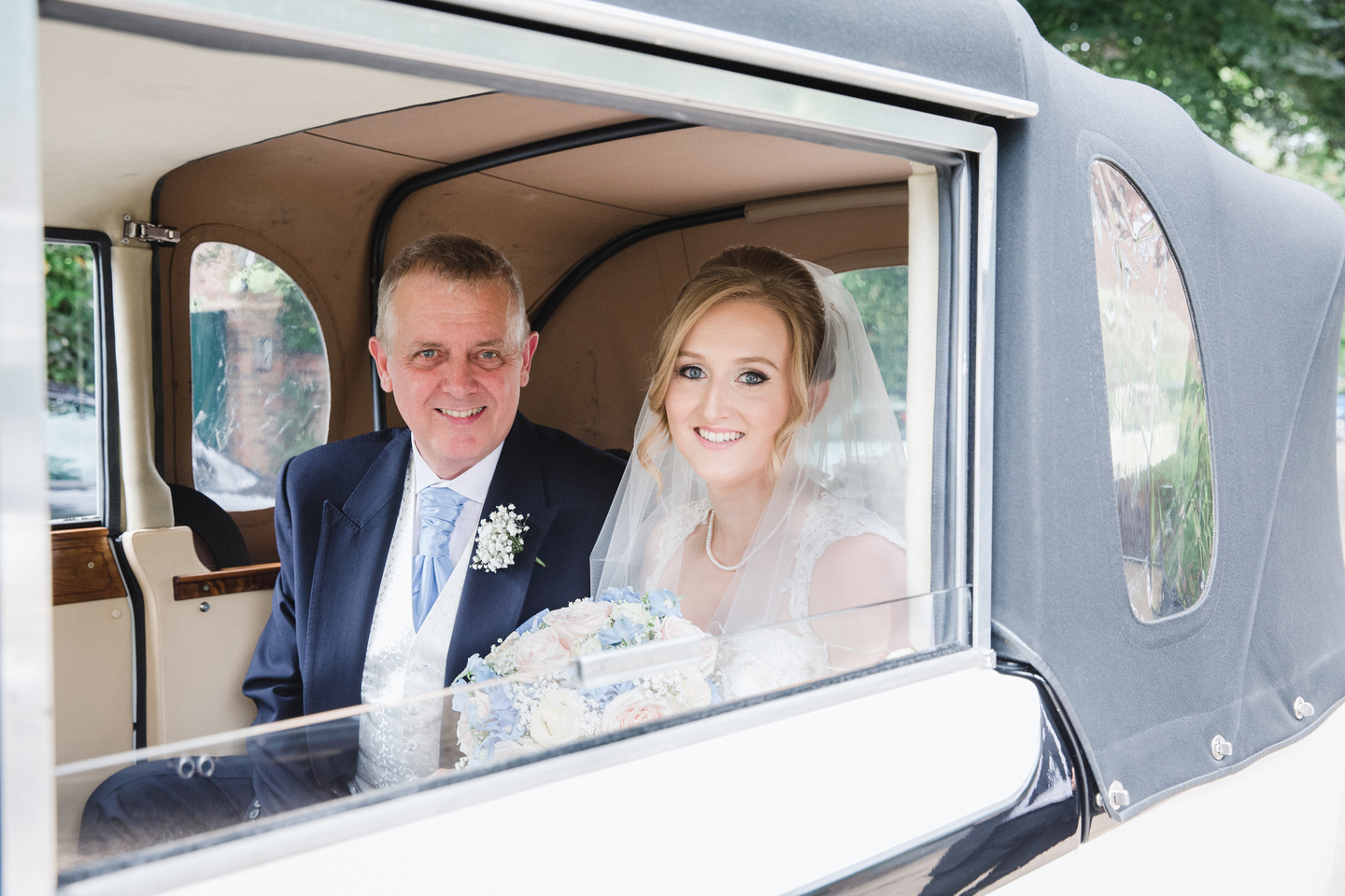 Father of the bride and bride in wedding car