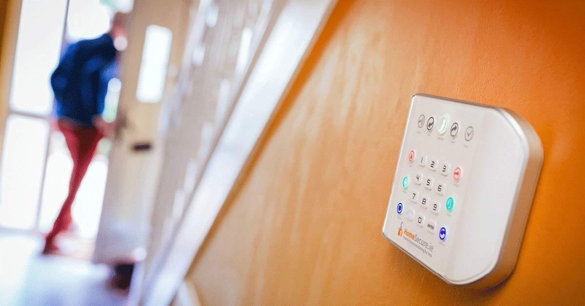 man leaving home, alarm panel on wall