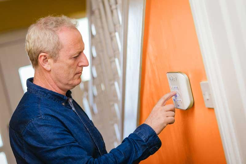 man at home alarm system keypad