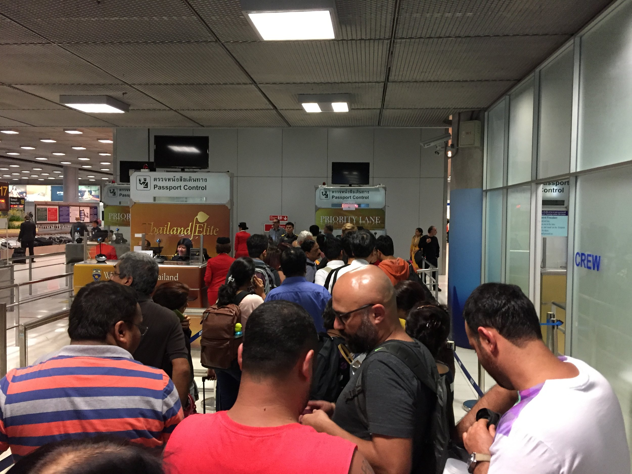 Irate travelers wait in the immigration line to be re-accepted for entry to Thailand and shuttled to a hotel.