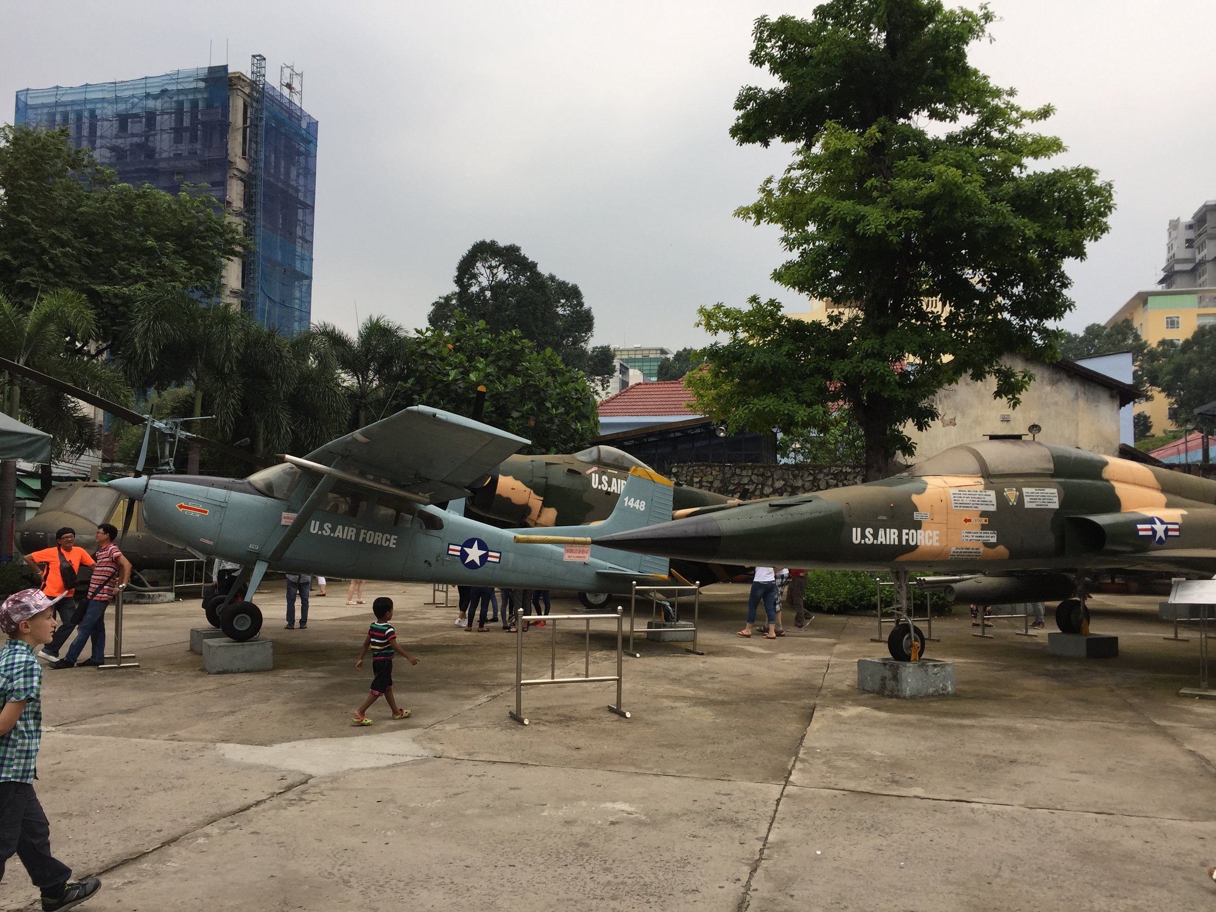Tourists pose with aircraft and tanks outside of the museum before entering and seeing what they were used to do.