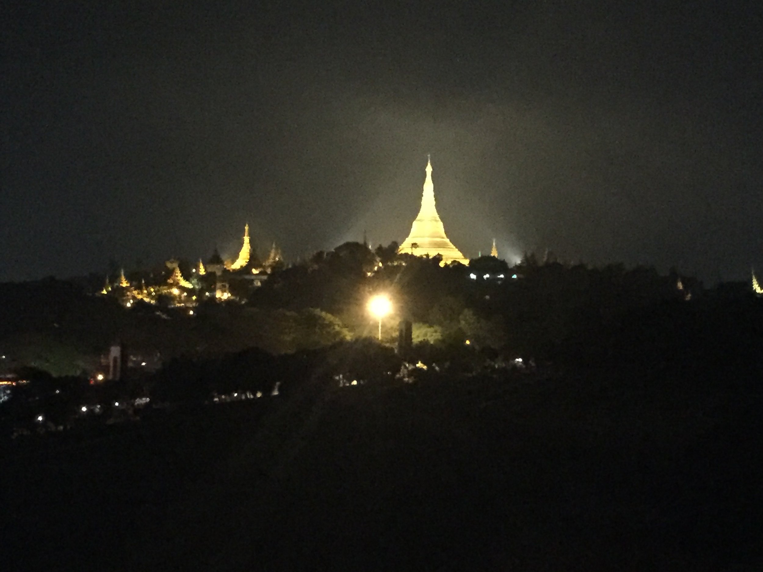Shwedagon seen from a kilometer away, changing colors through sunset and night.