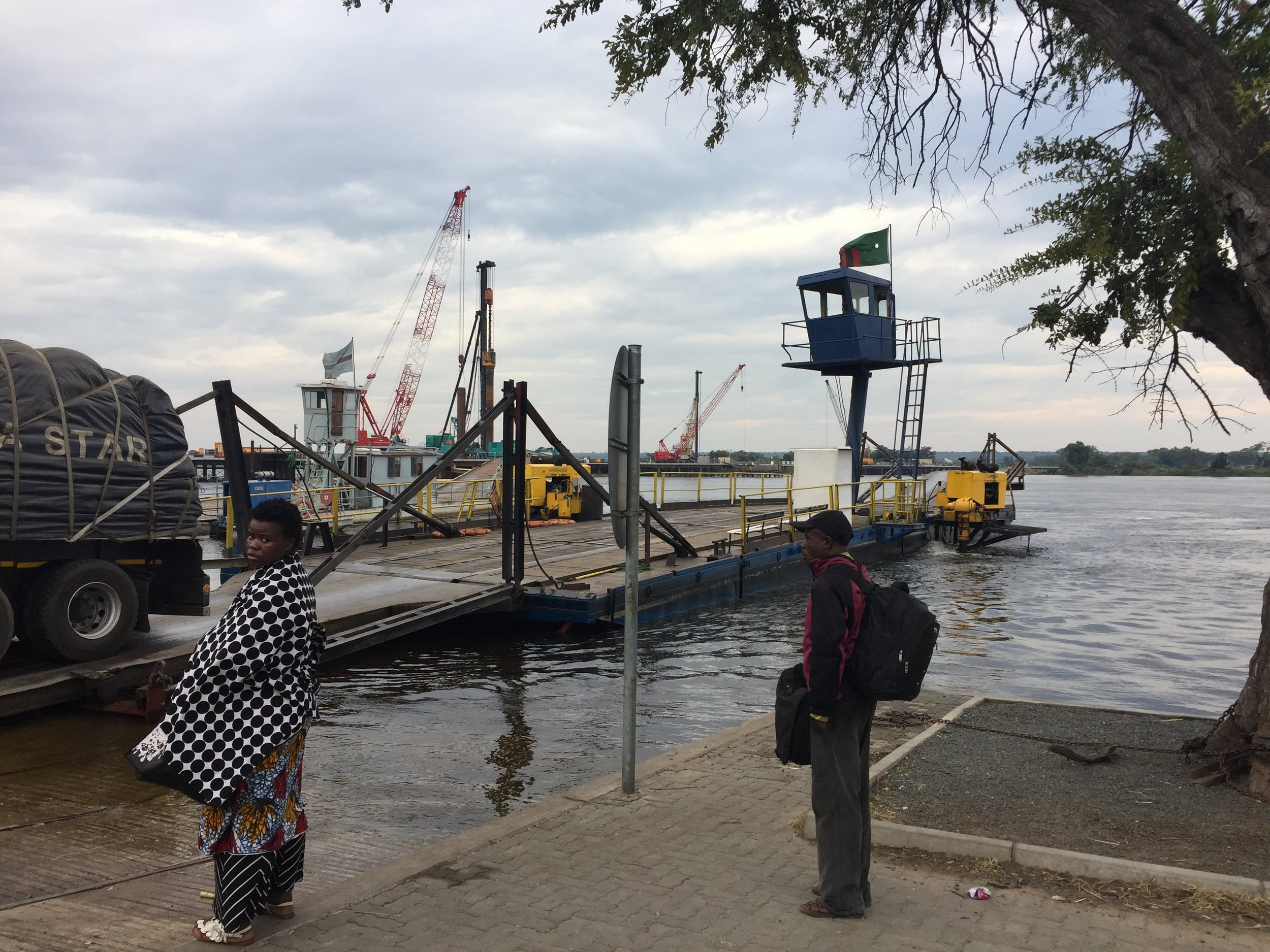 A woman wrapped in her floral dress and a blanket for the chilly morning waits alongside the Kazungula Ferry, while a big rig disembarks from the Zambia side.