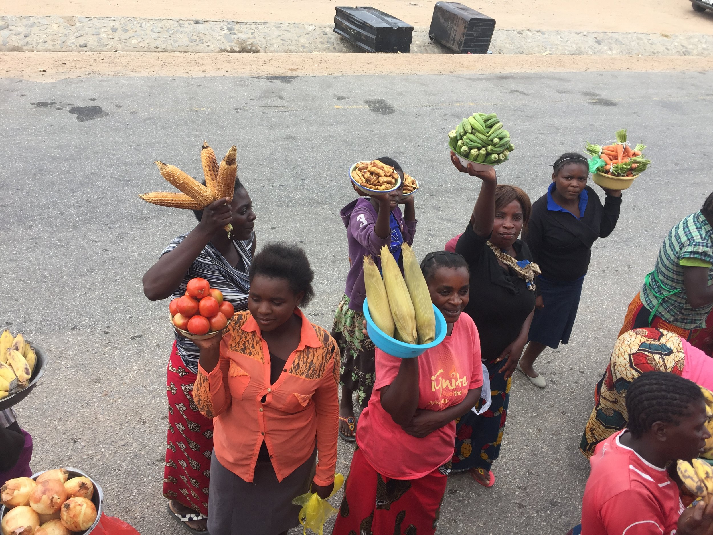 Women rush the side of the bus and reach up to sell fruits and vegetables to travelers.