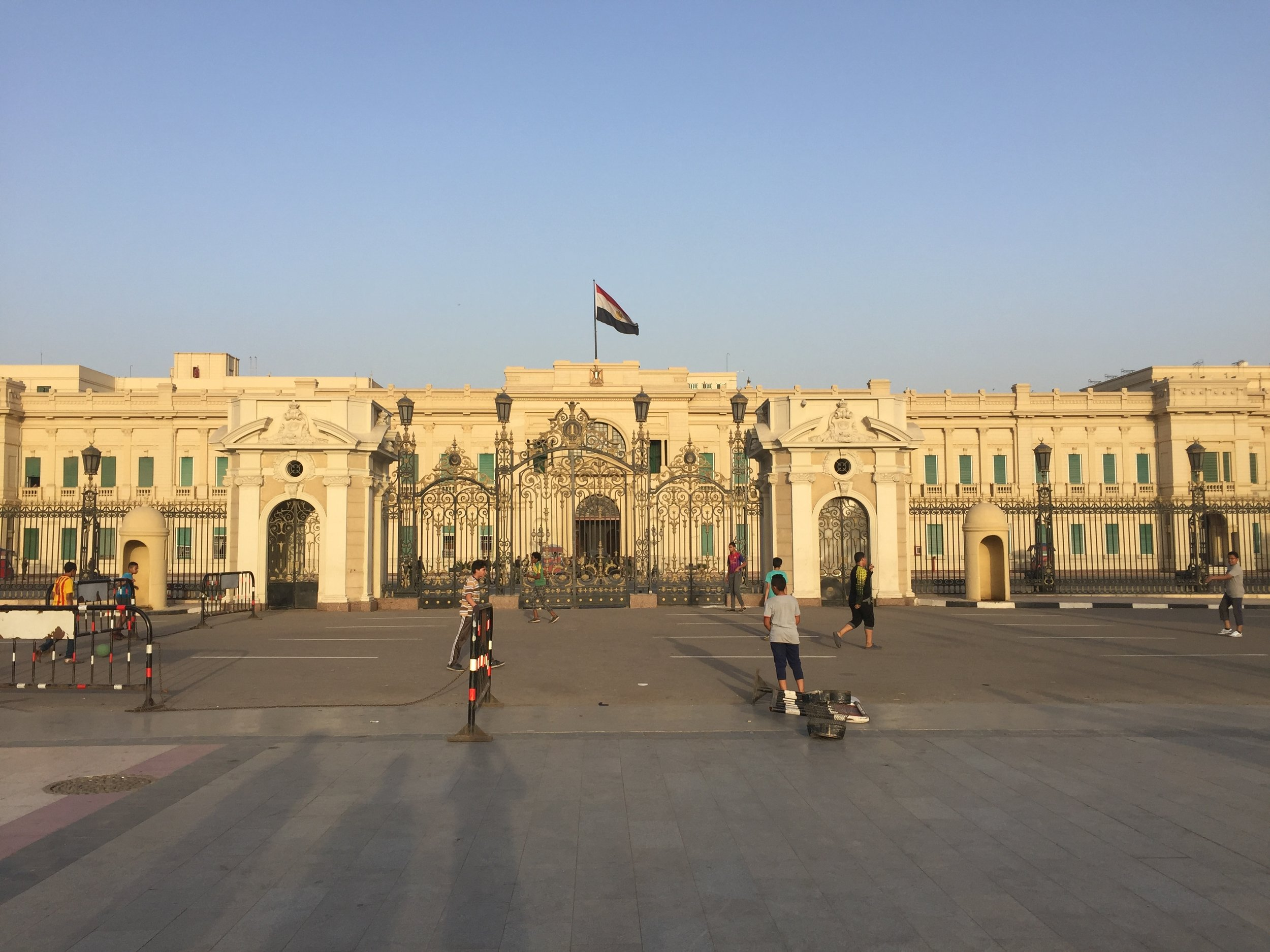 Kids play soccer in front of the Abdeen Palace, while military guards watch on. The front of the palace, normally busy with people, stands almost deserted now.