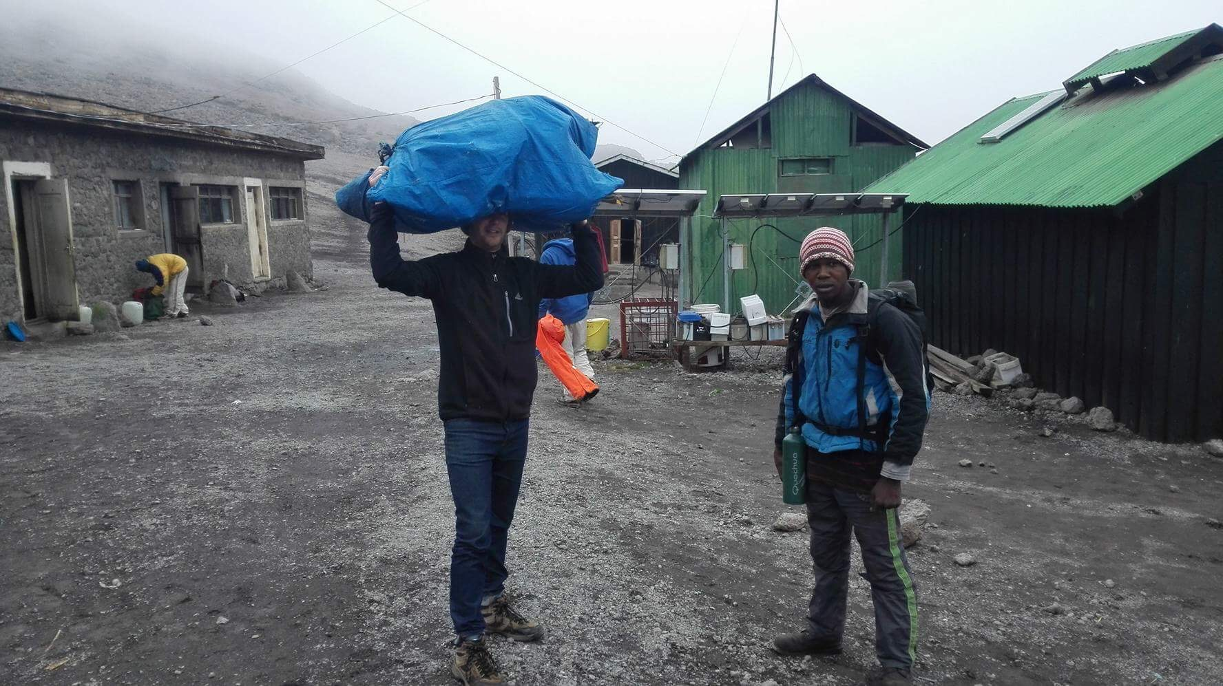 """""""Muzungu porter,"""" lifting the heavy load that porters carry up the mountain on their heads."""