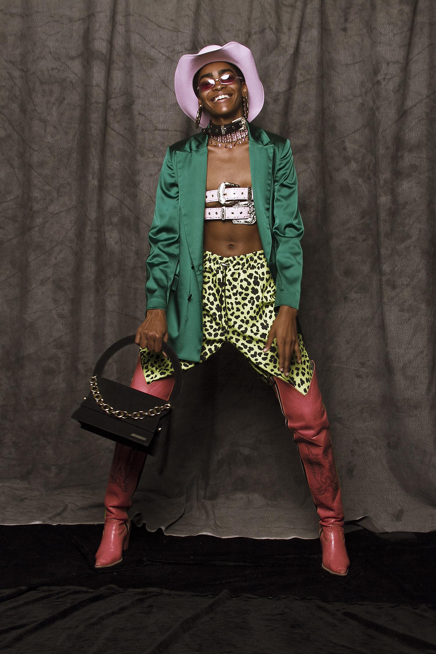 Blazer verde  Uterque,  cinturones vaqueros como top  NDA,  joggers de animal print  Forever 21,  botas rosas  AINT,  sombrero vaquero de la estilista, bolsa negra  Jacquemus,  choker negro  Zara,  choker rosa de la estilista, aretes  Forever 21,  lentes rosas de la estilista.