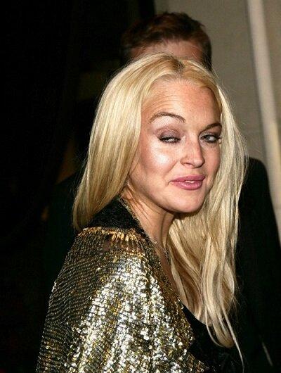 Una demacrada Lindsay Lohan sonríe de perfil a las cámaras.