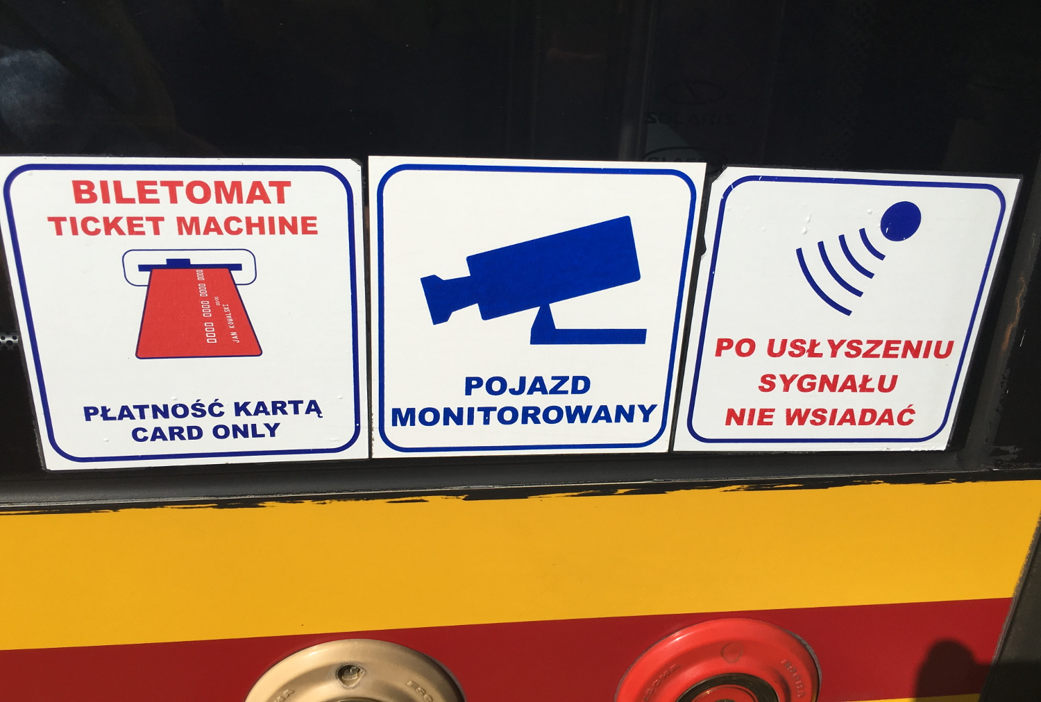 Stickers, like these, are on the side of the bus, near the middle doors. The first sticker (on the left) indicates that there's a ticket machine on-board.