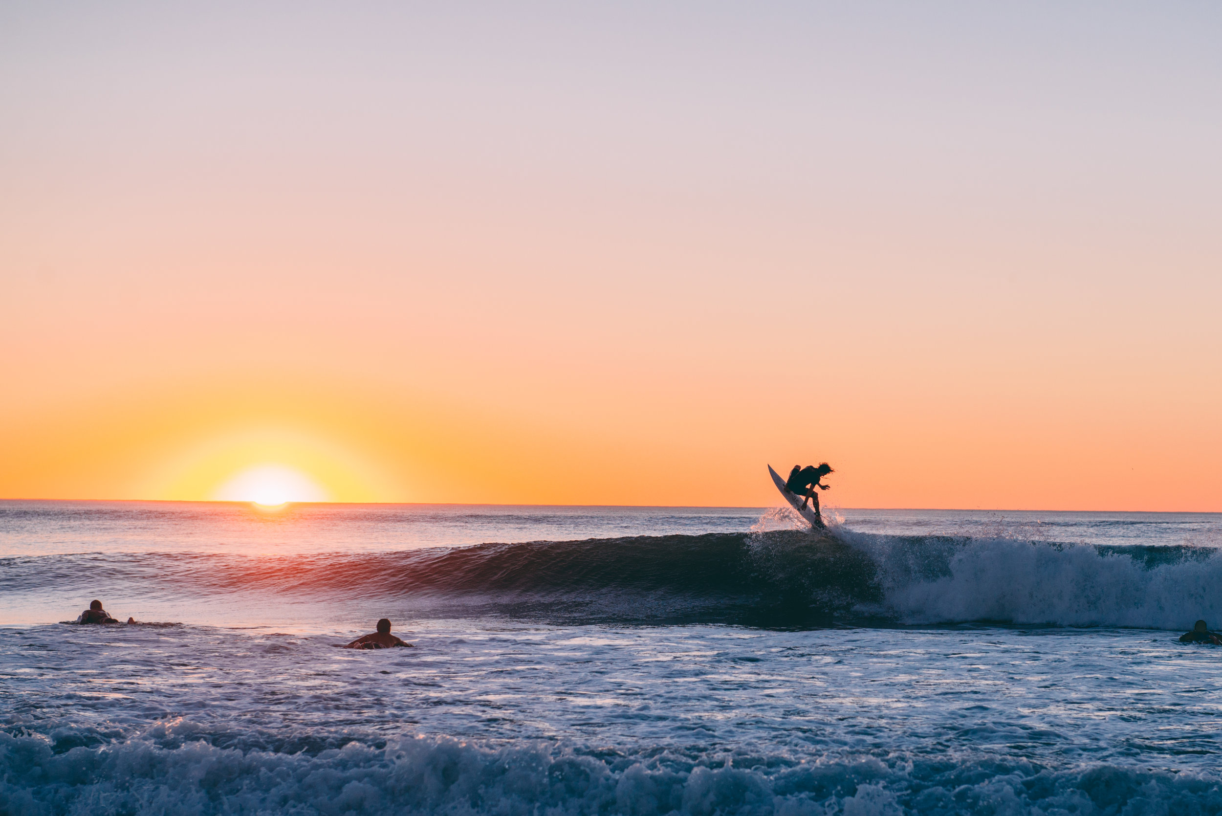 Tommy boosting a sunset alley up during an evening session at Le Penon