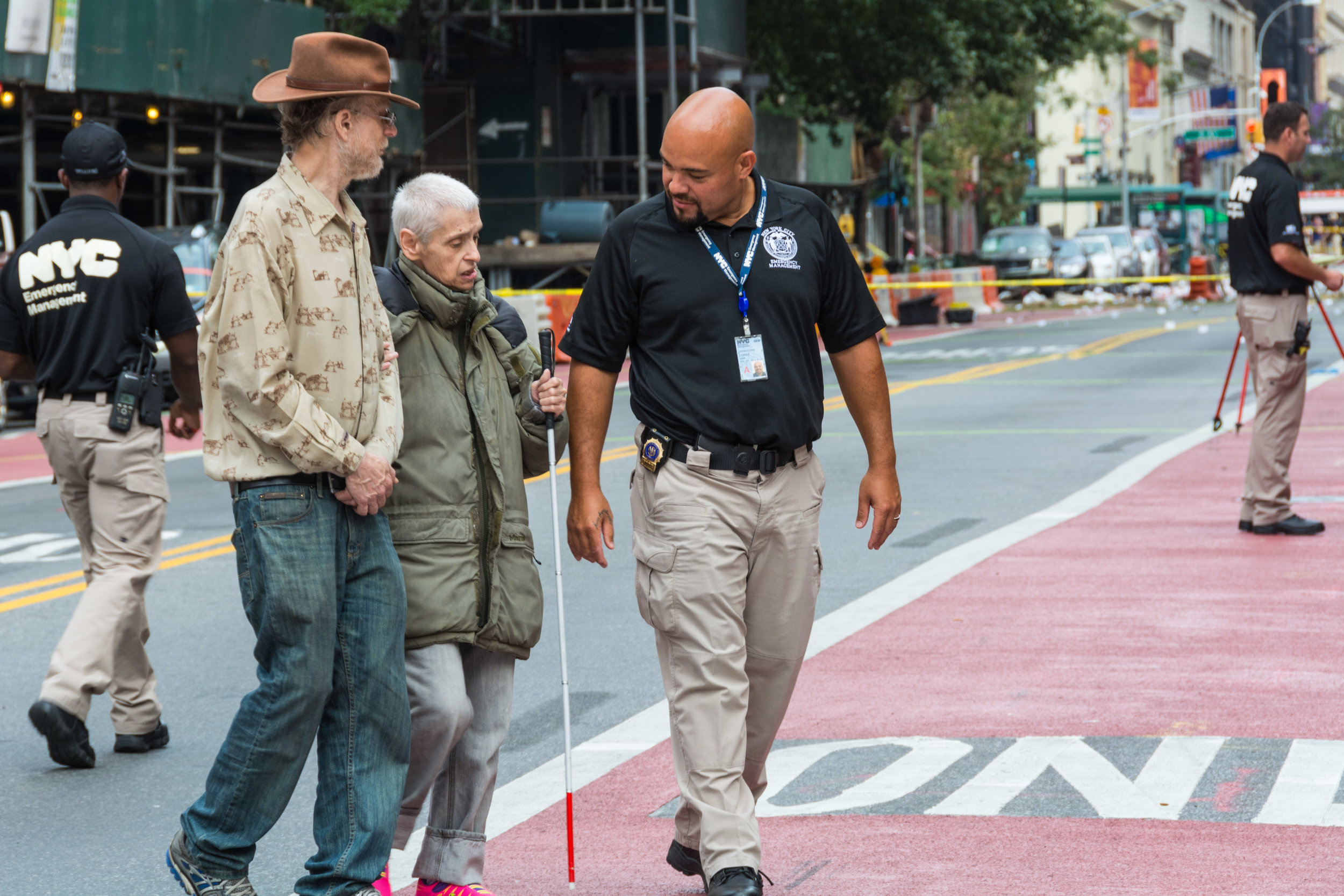 NYPD detective helps a blind resident of a nearby building Sunday afternoon.