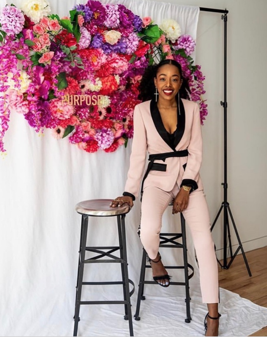 Fashion lover and inspirational speaker Sade chose a more formal look with a ribbon belt and feathered open-toed shoes to host her Purpose Push Her event in NYC. -