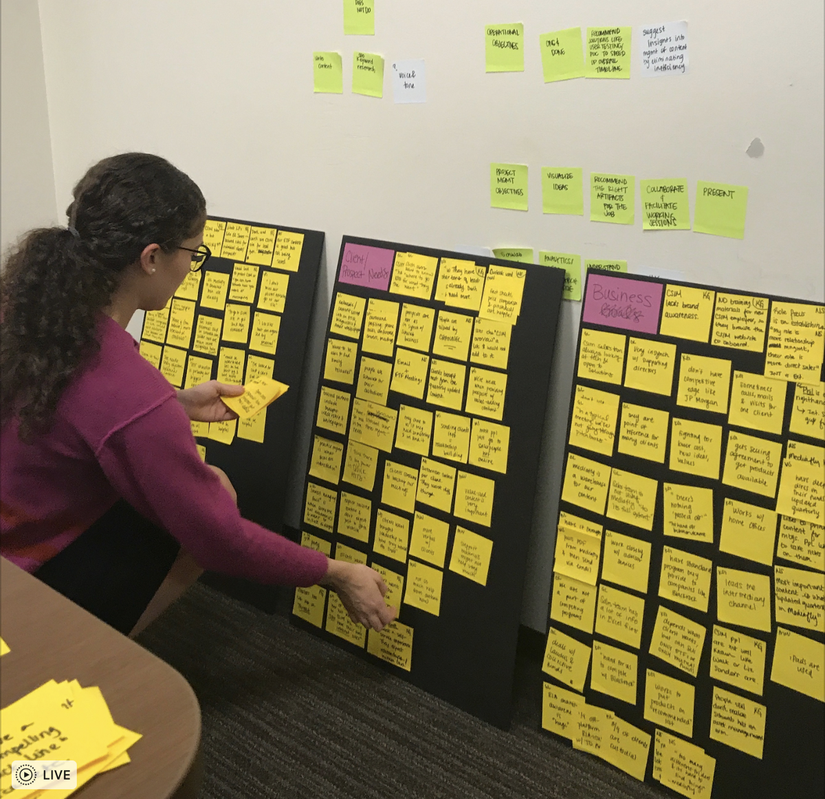 My old team mate, Luna, sorting through user interview insights on sticky notes.
