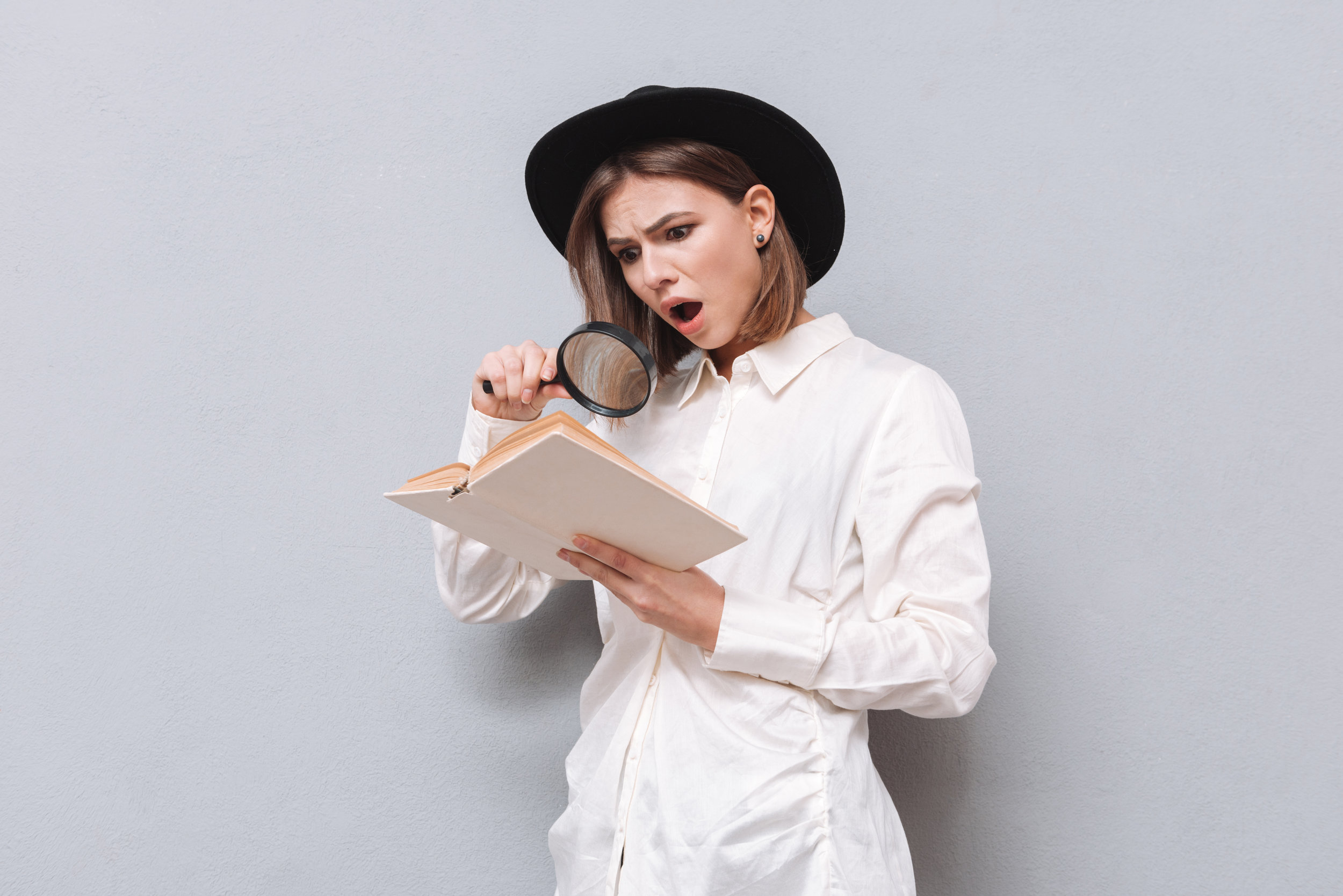 shocked woman reading book with magnifying glass