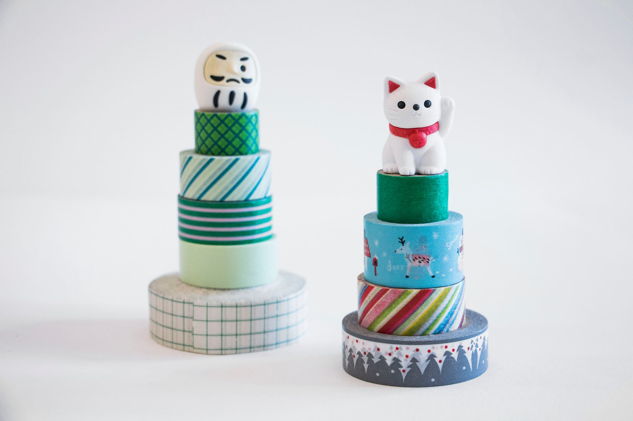 Daruma and Lucky Cat sitting on top of my washi tape stack.