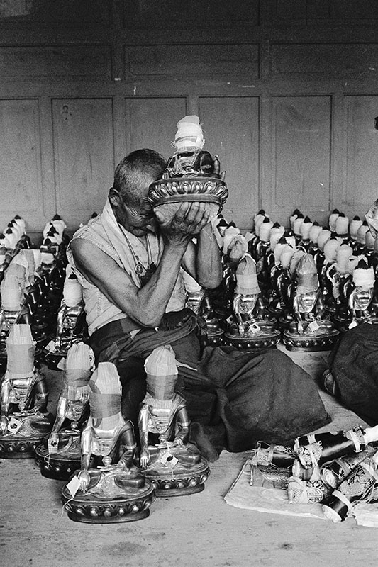 An old monk placing treasures inside Buddha statues, Sichuan