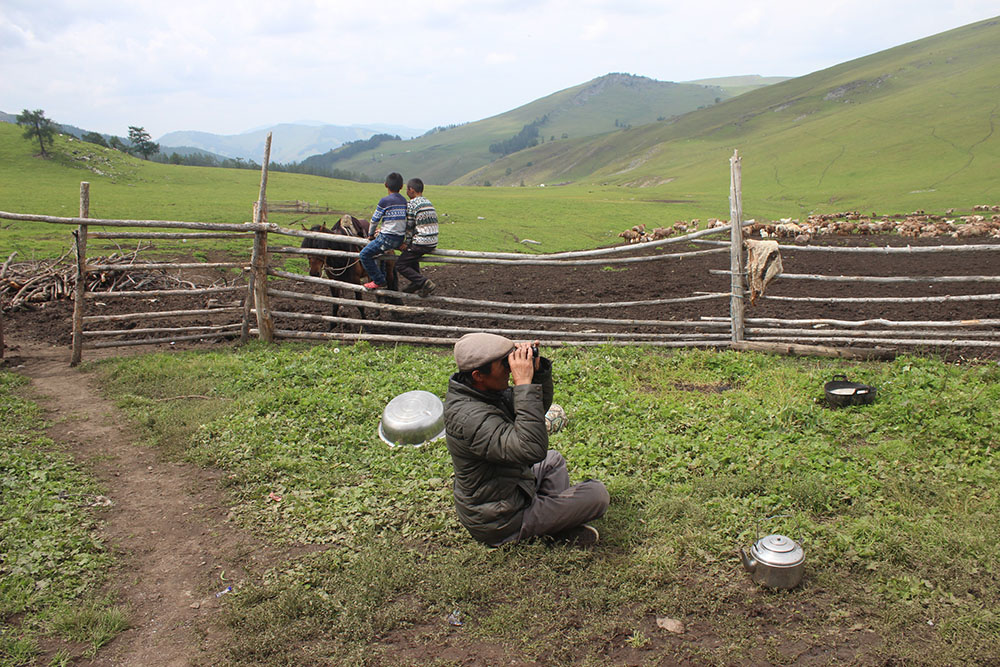Uncle sitting at the gate, watching his sheep through the binoculars. (by Huerman)