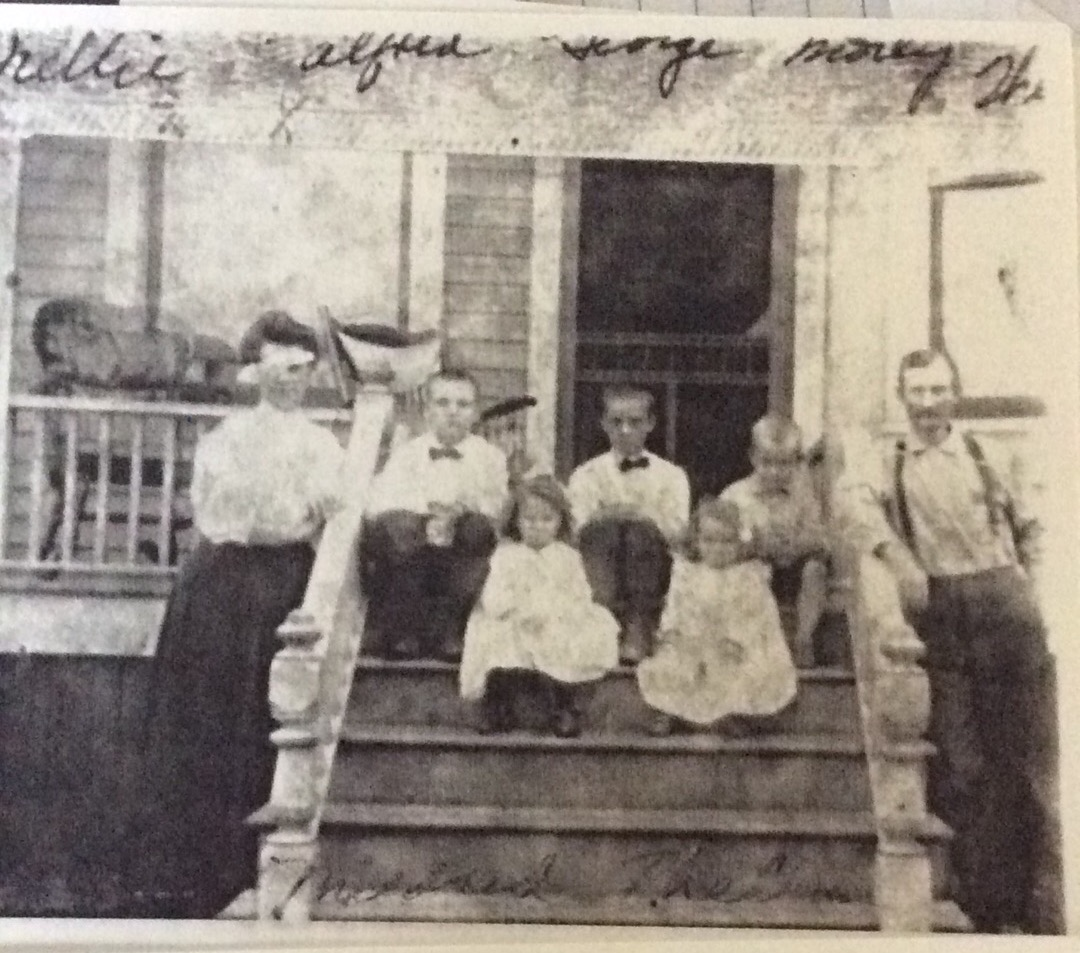 Thelma (front row on the right) sitting with 4 of her siblings, flanked by their parents, Nelllie and James. The boys (left to right) are: Alpheus, George, and Morely. Mildred is next to Thelma. Likely at their home on Baldwin St. in Detroit, MI.