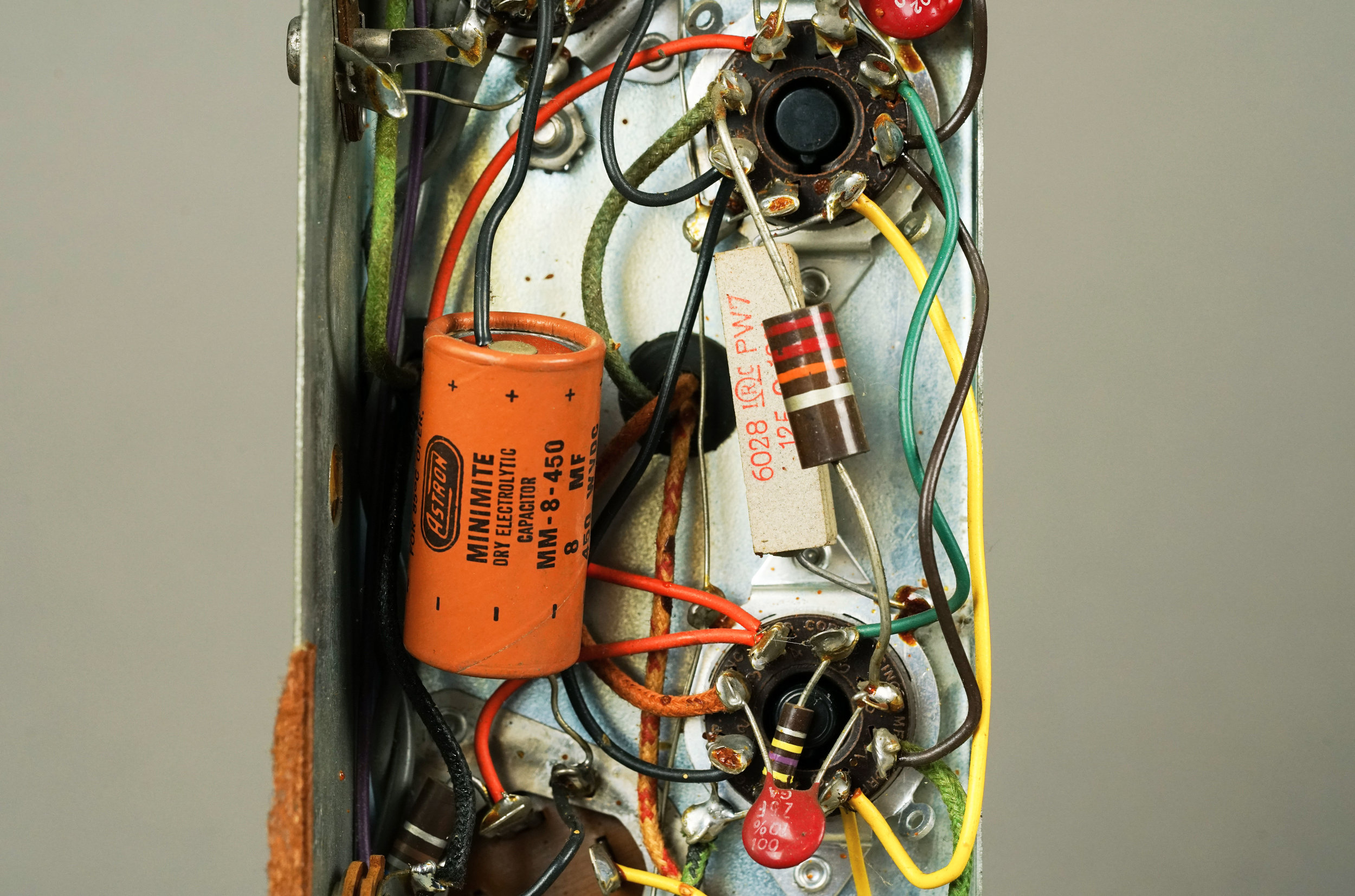 Note the Astron Minimite electrolytic capacitor in this original  Wurlitzer 700  amplifier. The leads are very long, which is convenient for mounting in a point-to-point circuit like this one. On the right, there is a 7 watt wirewound resistor as well as a high-wattage (probably 2 watts) carbon composition resistor.
