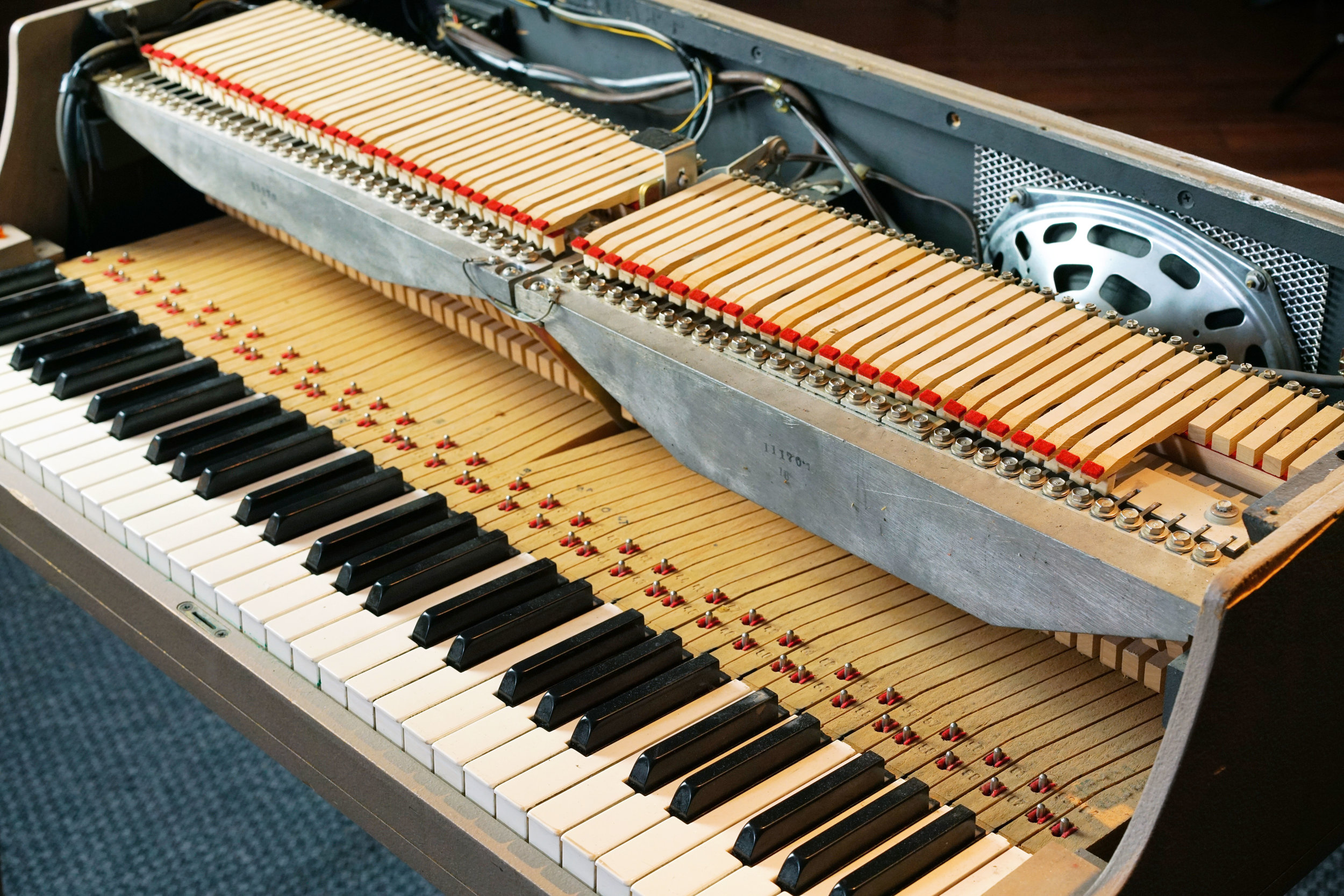With the lid of this Wurlitzer 140b off, you can clearly see the keyboard's mechanical action. The reeds and the harp are also partially visible in this photo, particularly in the treble section where the dampers are abbreviated. In this model, the amplifier is located at the back (where the wires at the back left lead).