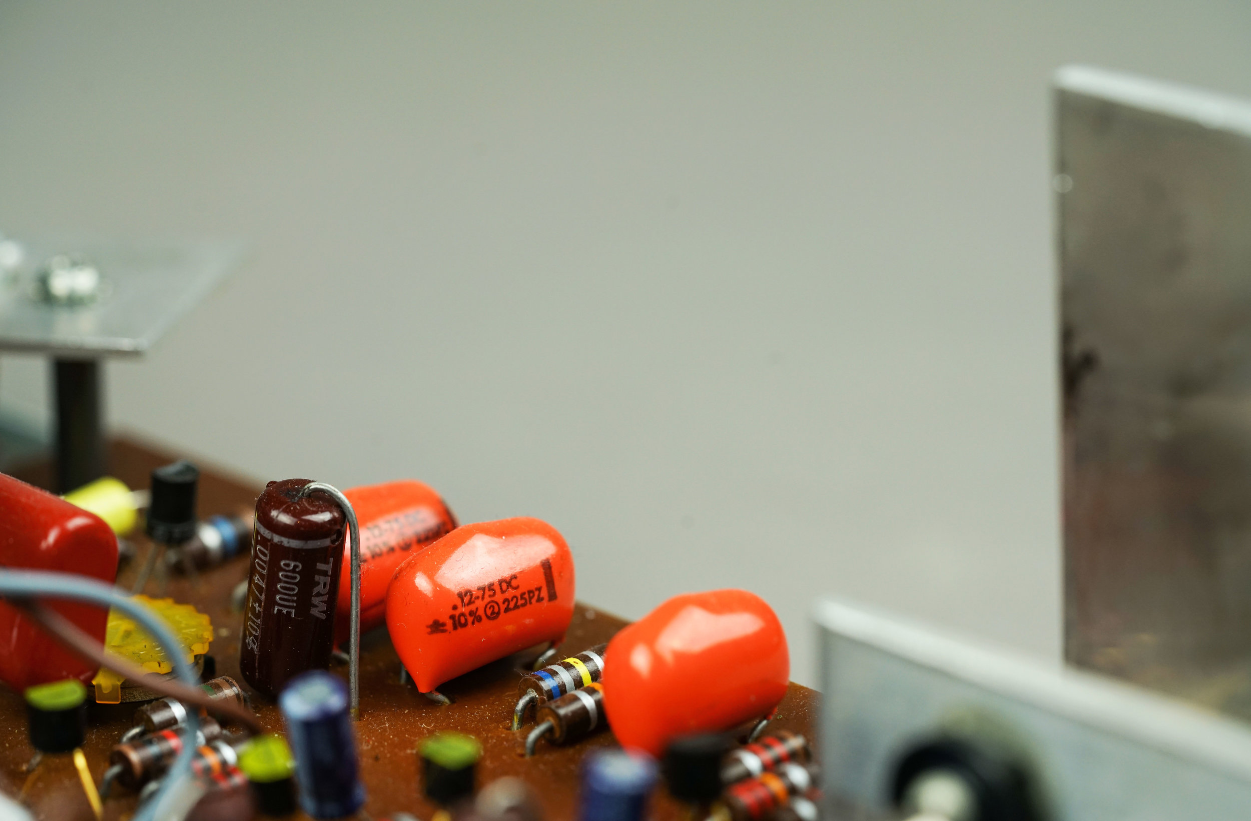 The orange capacitors are the tremolo capacitors in a Wurlitzer 200. They provide the phase shift that allows the circuit to oscillate.