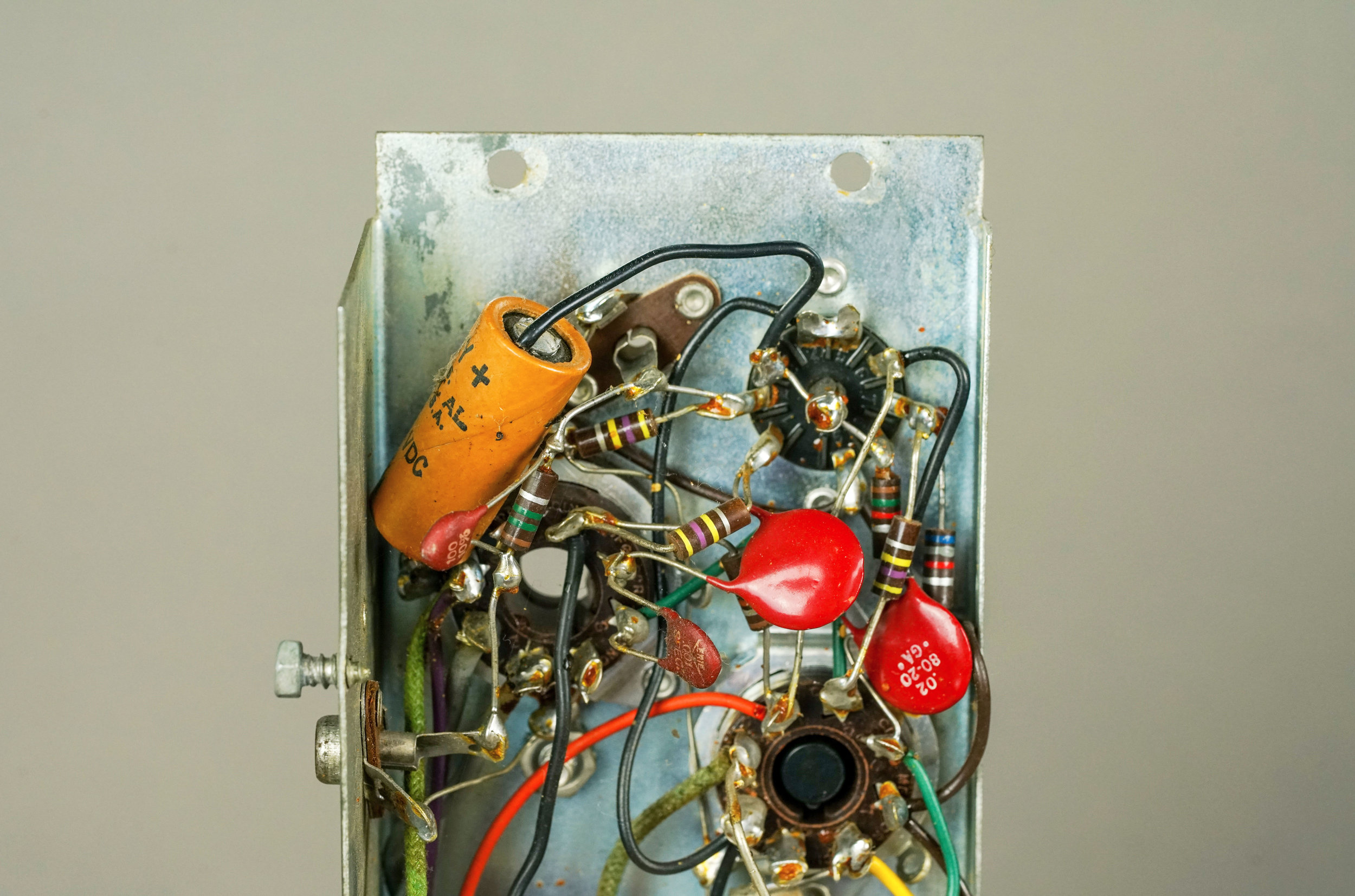 In this Wurlitzer 700 amplifier, the heater wires are black and brown. In this photo, the black wire starts at pins 4 and 5 of the 12AX7, while the brown wire starts at pin 9. This is not an optimal way to wire heaters, because the circuit is not center-tapped and the wires are not twisted.