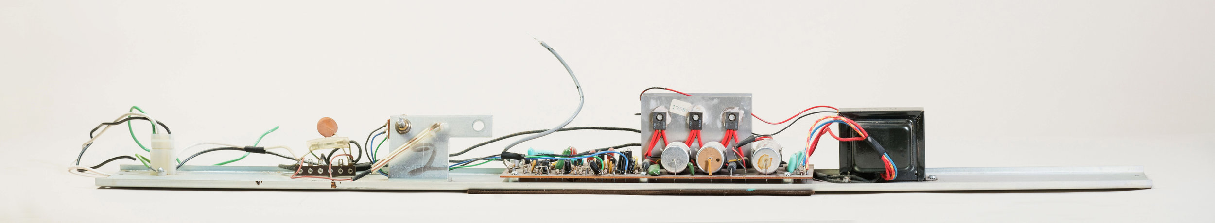 In the Wurlitzer 200, the power transformer is mounted on the right side of the amp rail, close to the rectifier. However, the mains wiring and the power switch are mounted on the left side of the amp rail. For this reason, the black transformer wires are extremely long in this amp, and must travel past the preamp area. Make sure they're not too close to any sensitive preamp components.