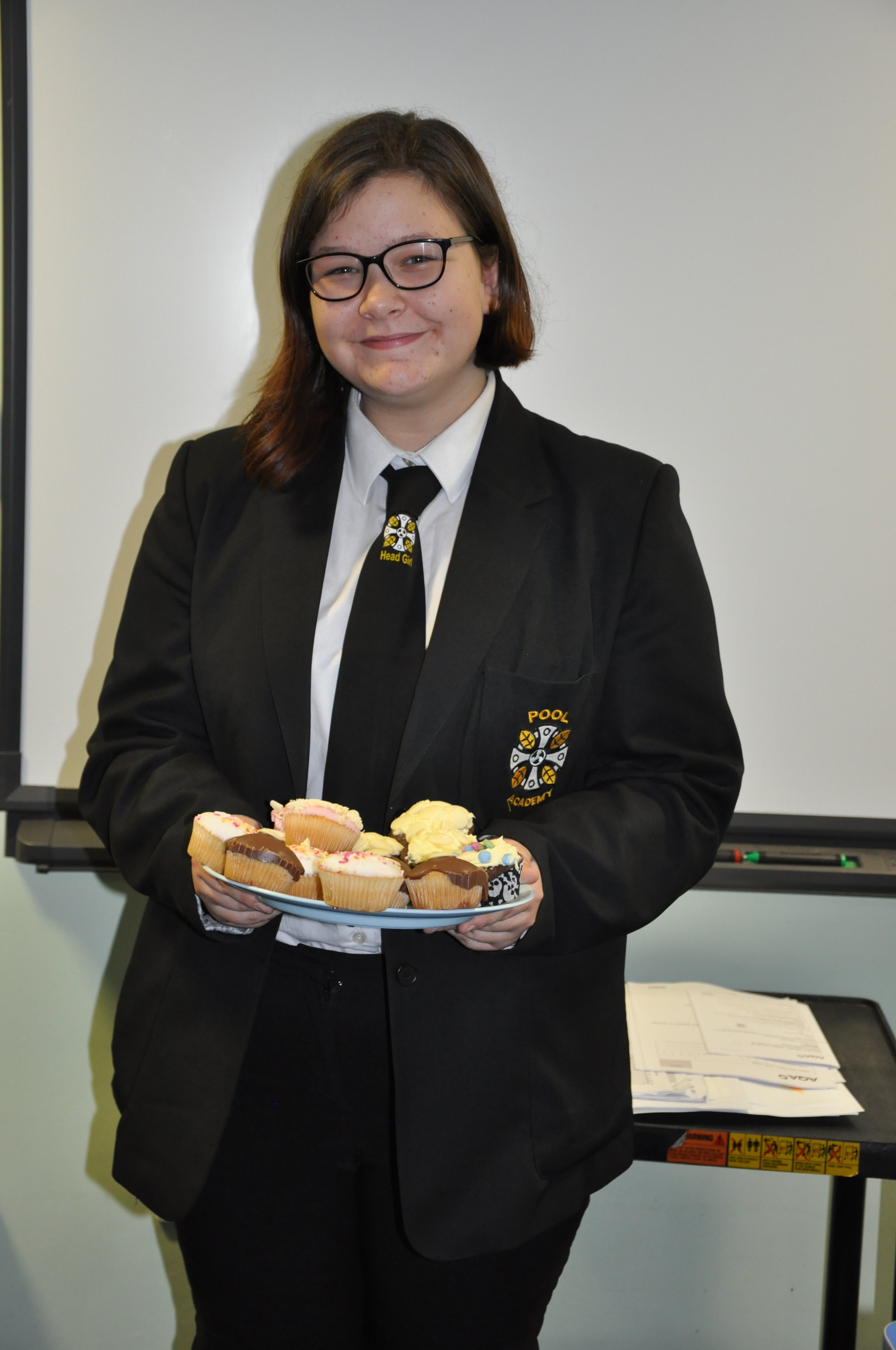 Head Girl with some of the cakes on sale at the bake sale last term.