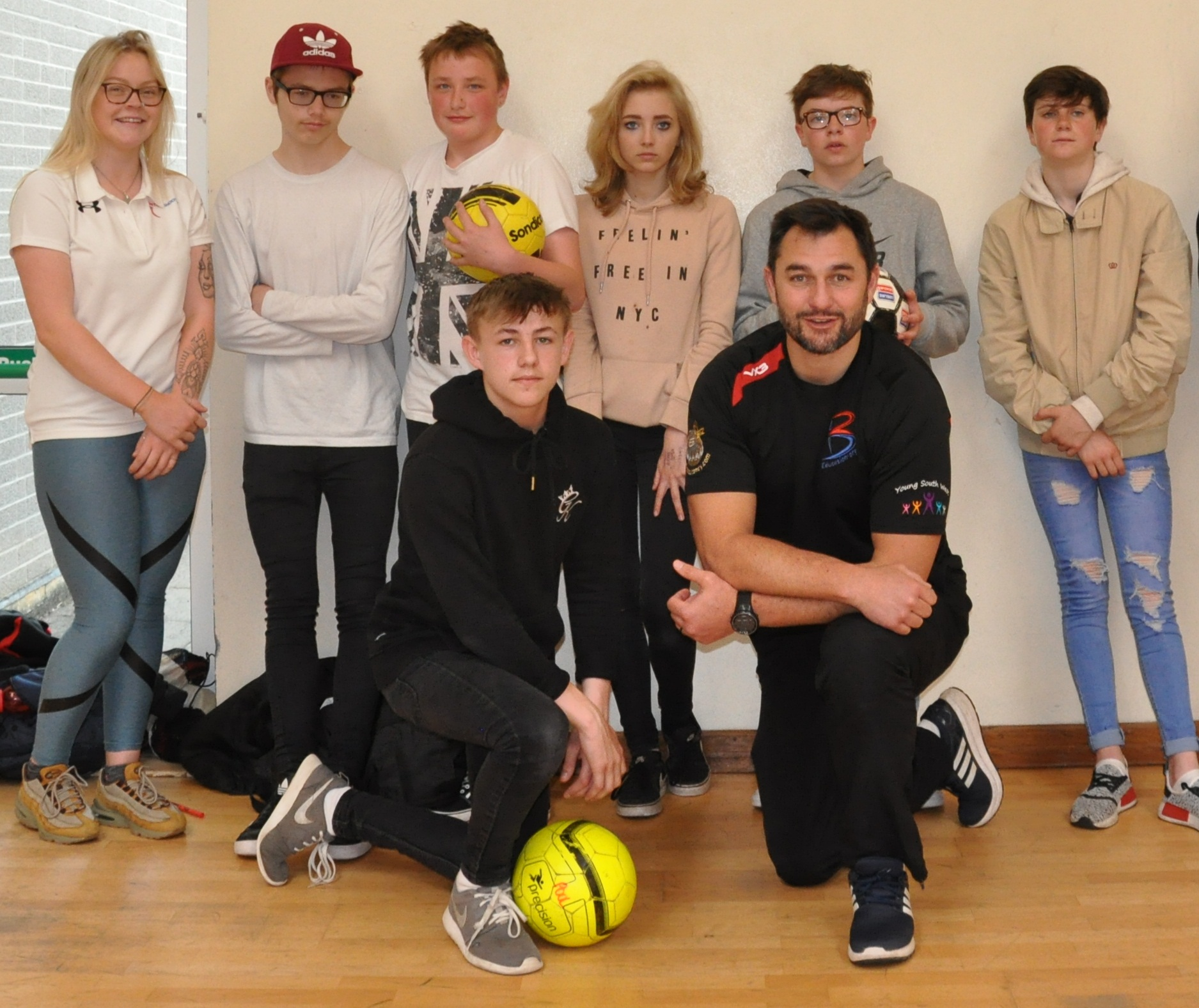 Photograph caption:  Thinus Delport, international Rugby player, with students from Pool Academy.