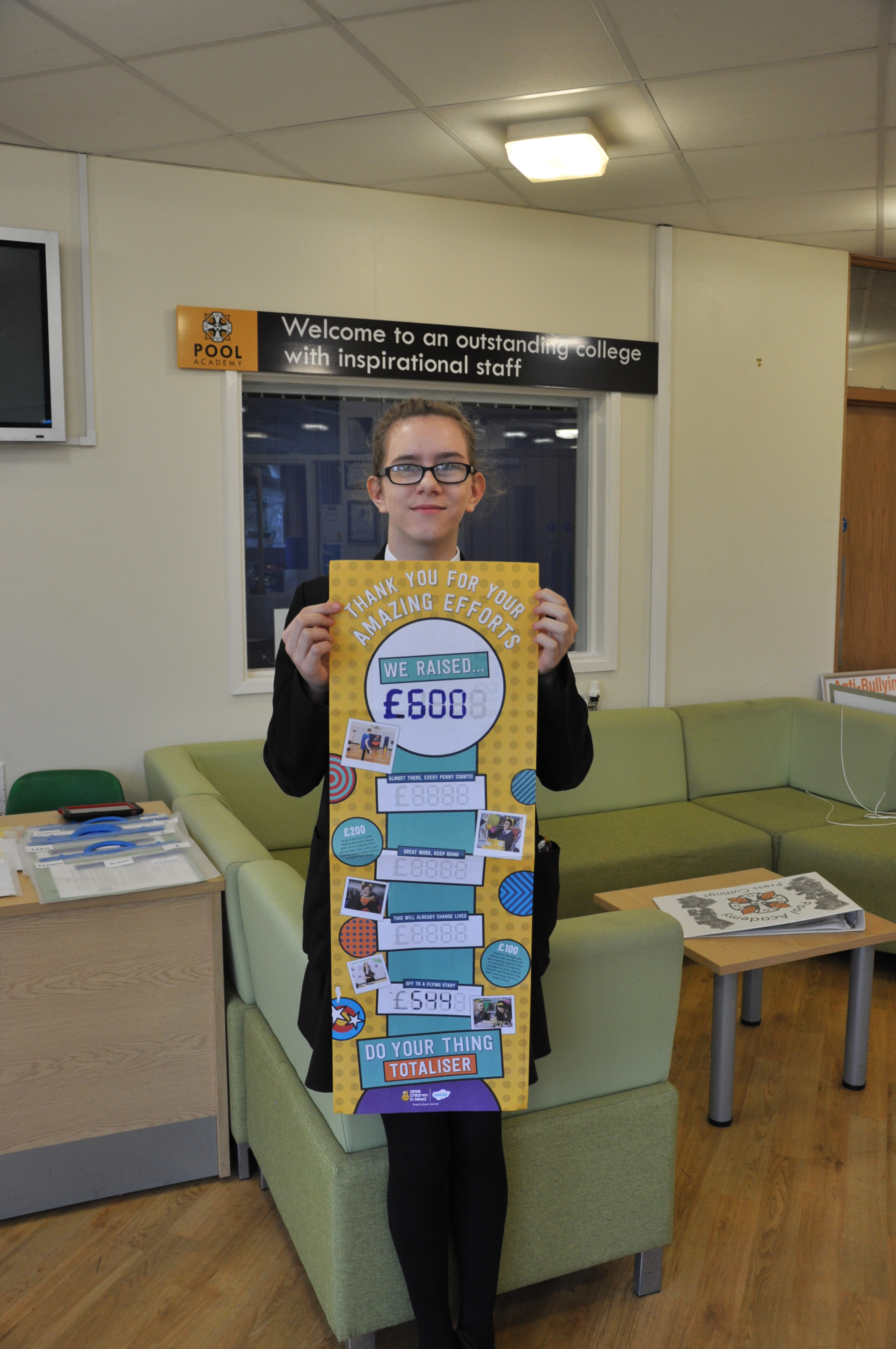 Nicole with a poster showing the total amount raised.