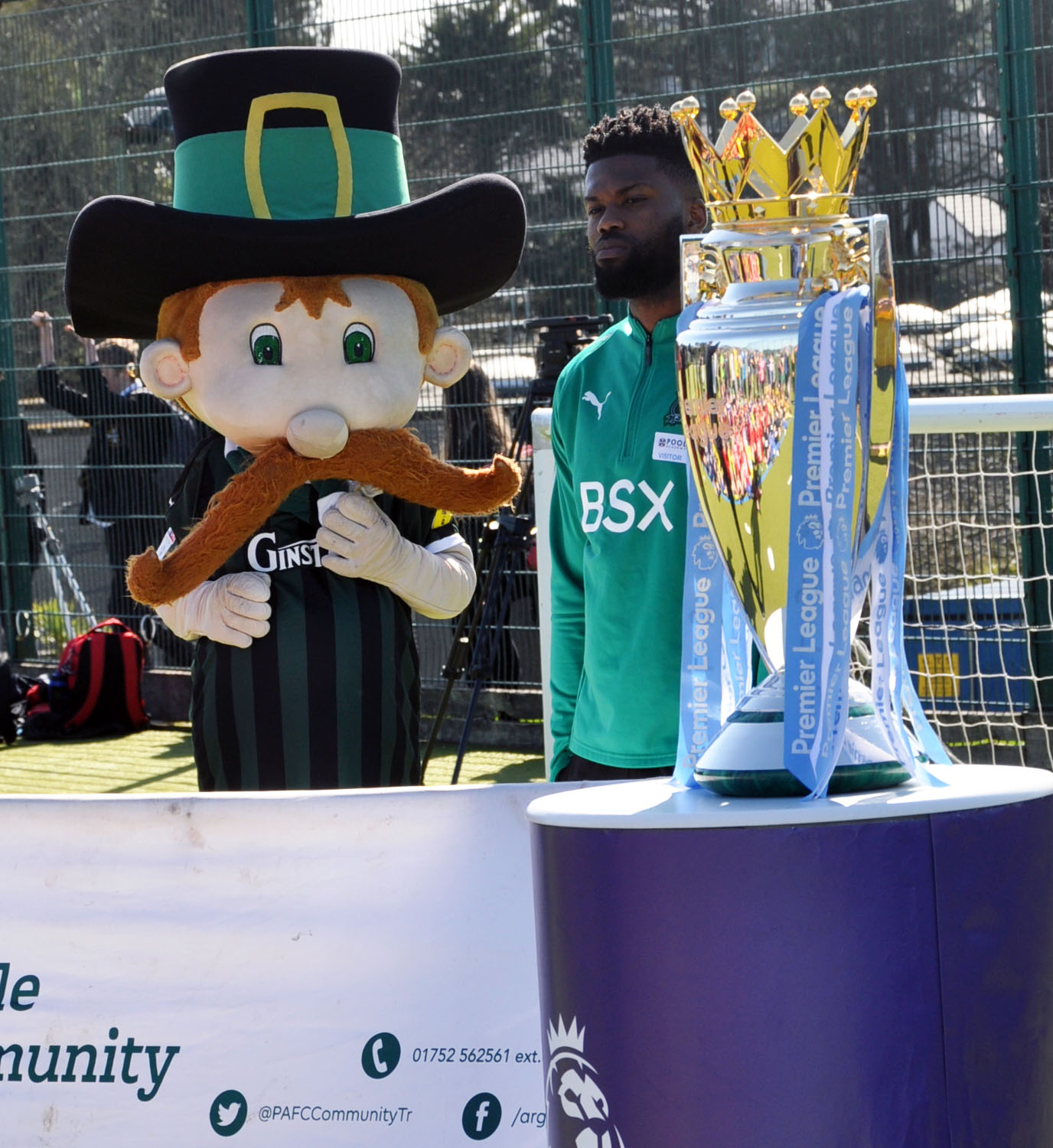 Plymouth Argyle player Joel Grant with mascot Pilgrim Pete and the Premier League Cup.