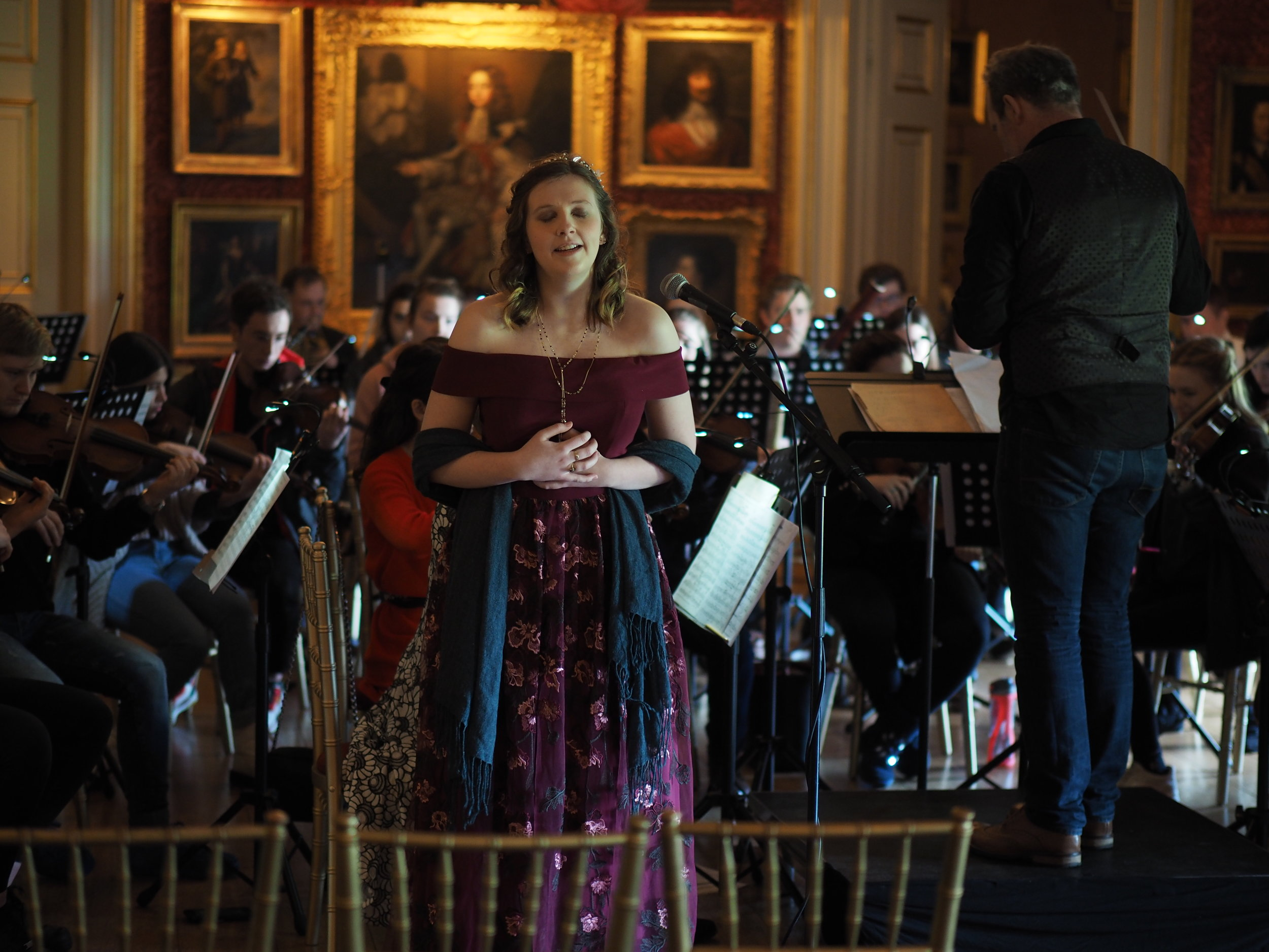 Photograph:  Kiera singing in the ballroom of Goodwood House. Photograph taken by Andrew Worsfold