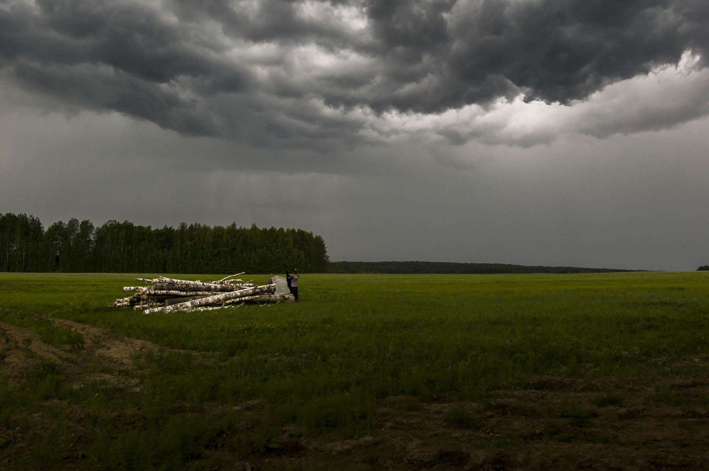 Pilgrims pause to take precautions against the rain, Kirov region, June 2010