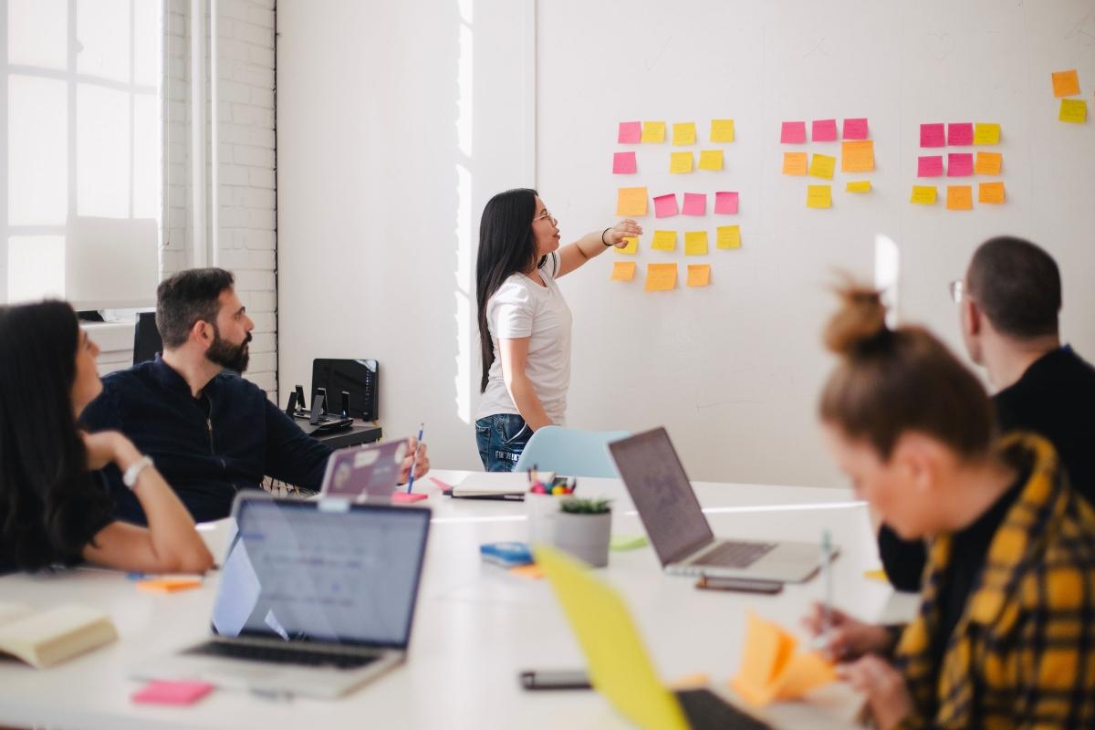 Female Offshore Software Developer Showing Her Agile Team Tasks on a Whiteboard