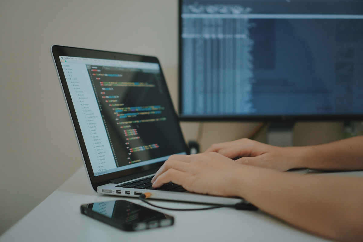 Mobile App Developer Writing Code on His Laptop