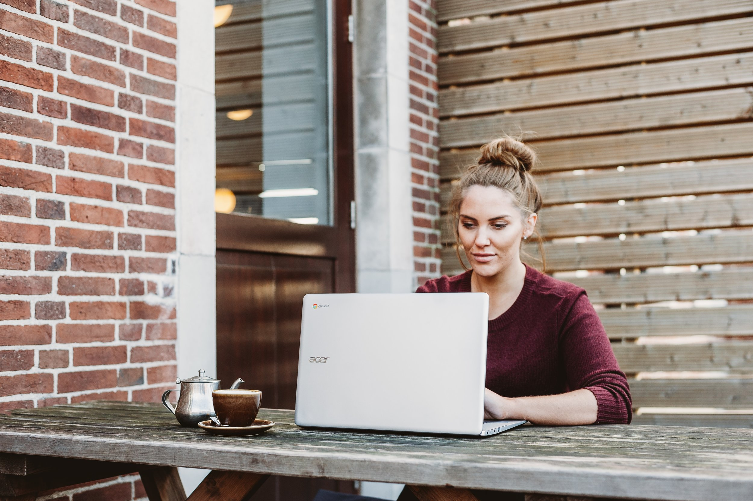 Woman Looking into WordPress for Small Business on Her Laptop Outside