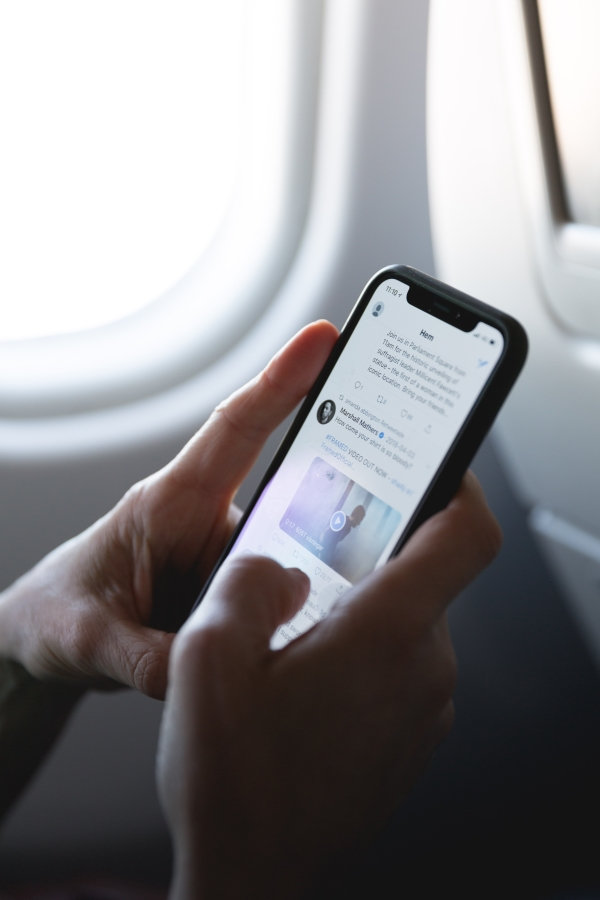 Person Holding Mobile Device while on Plane