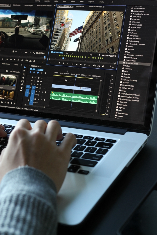 Graphic Designer Editing Video Footage on Laptop
