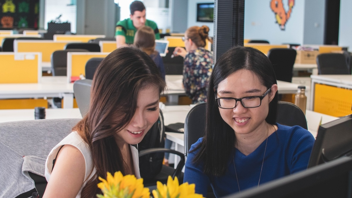 Female Scrum Master Working with a Female Software Developer at Her Desk