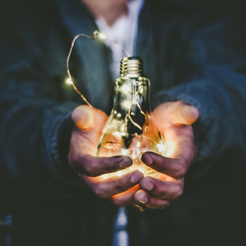 Man Holding Lightbulb in His Hands