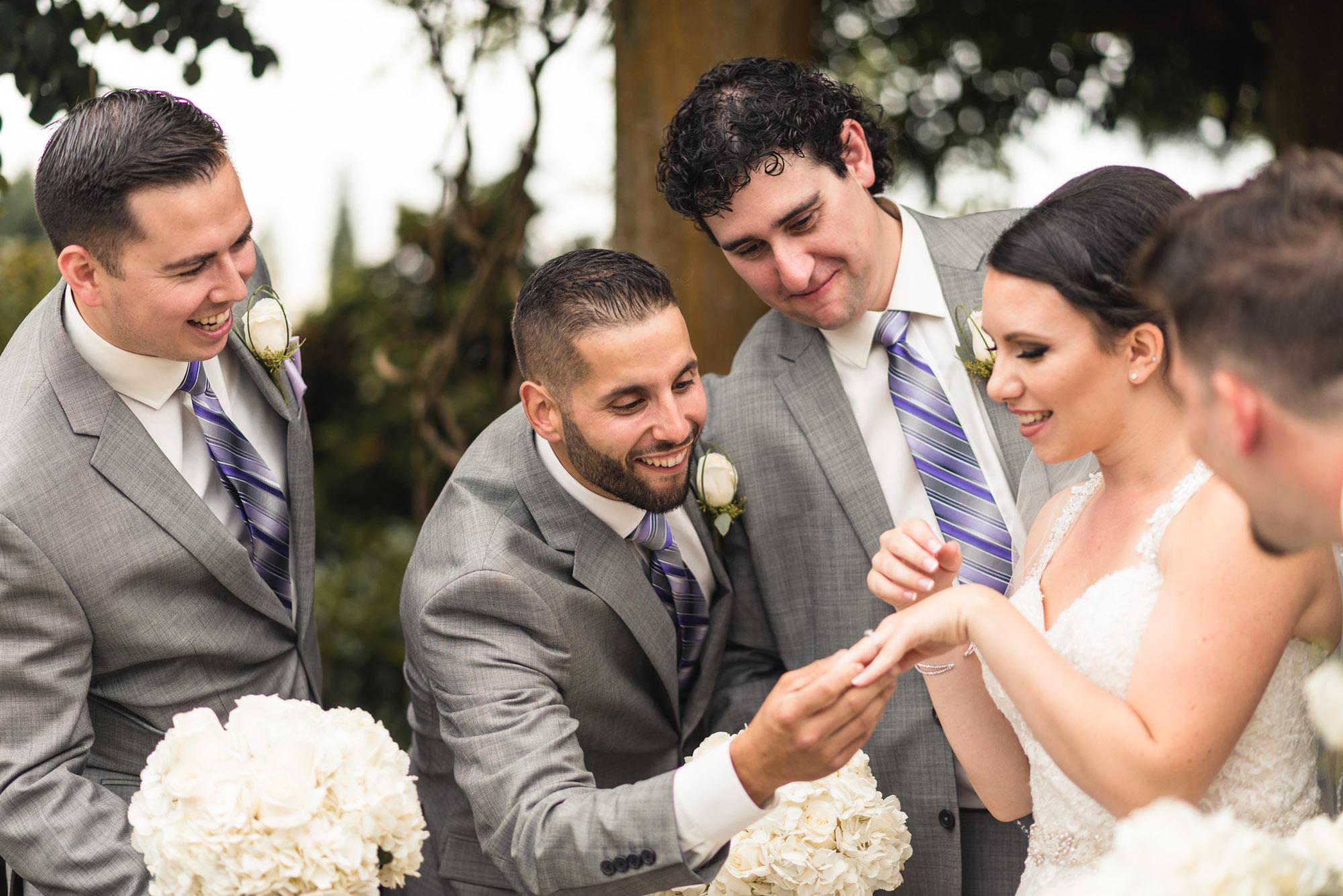 Groomsmen looking at Bride's ring